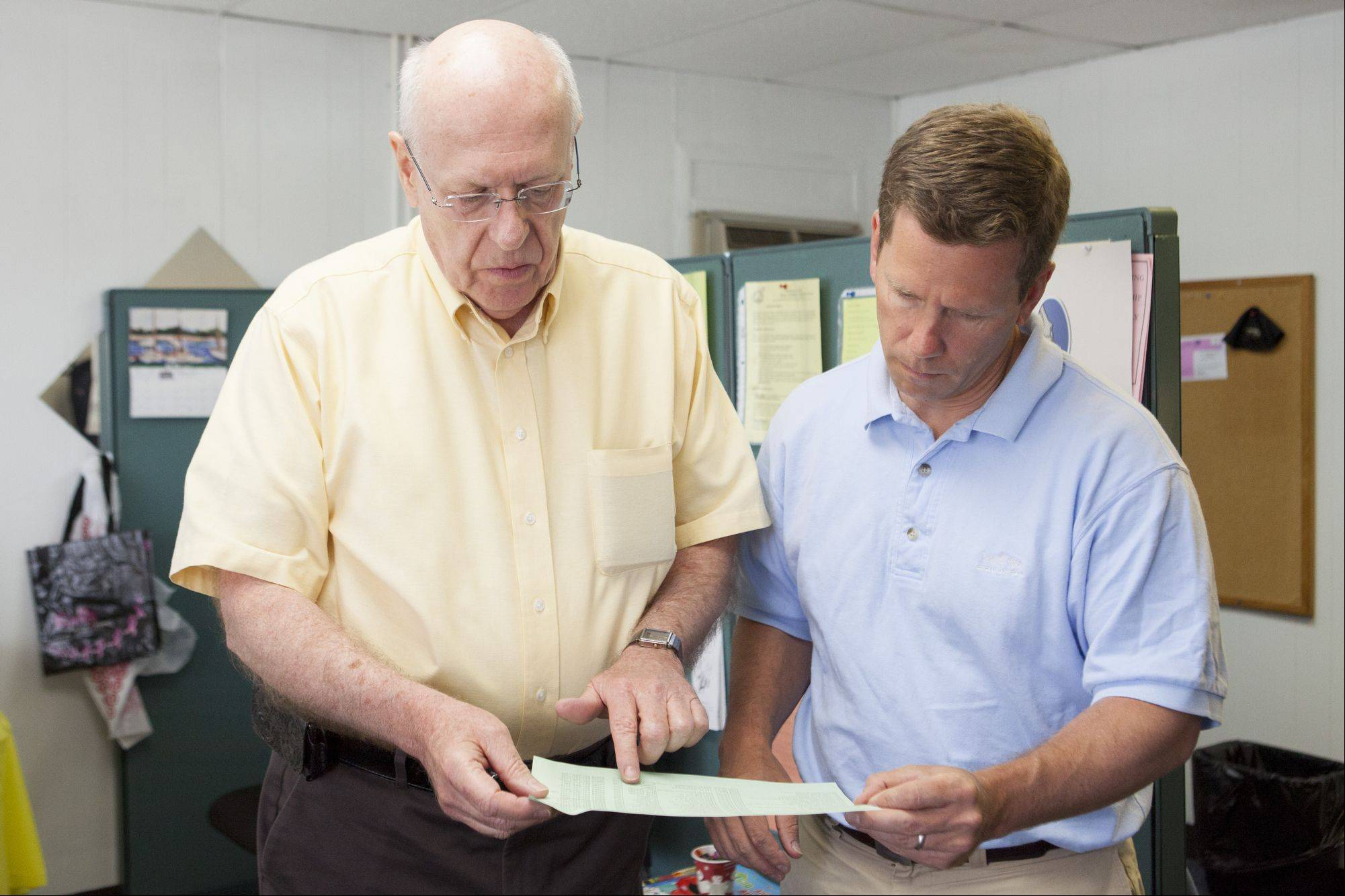 Jim Bradley shows a food schedule to Congressman Bob Dold, who visited the pantry on Monday.
