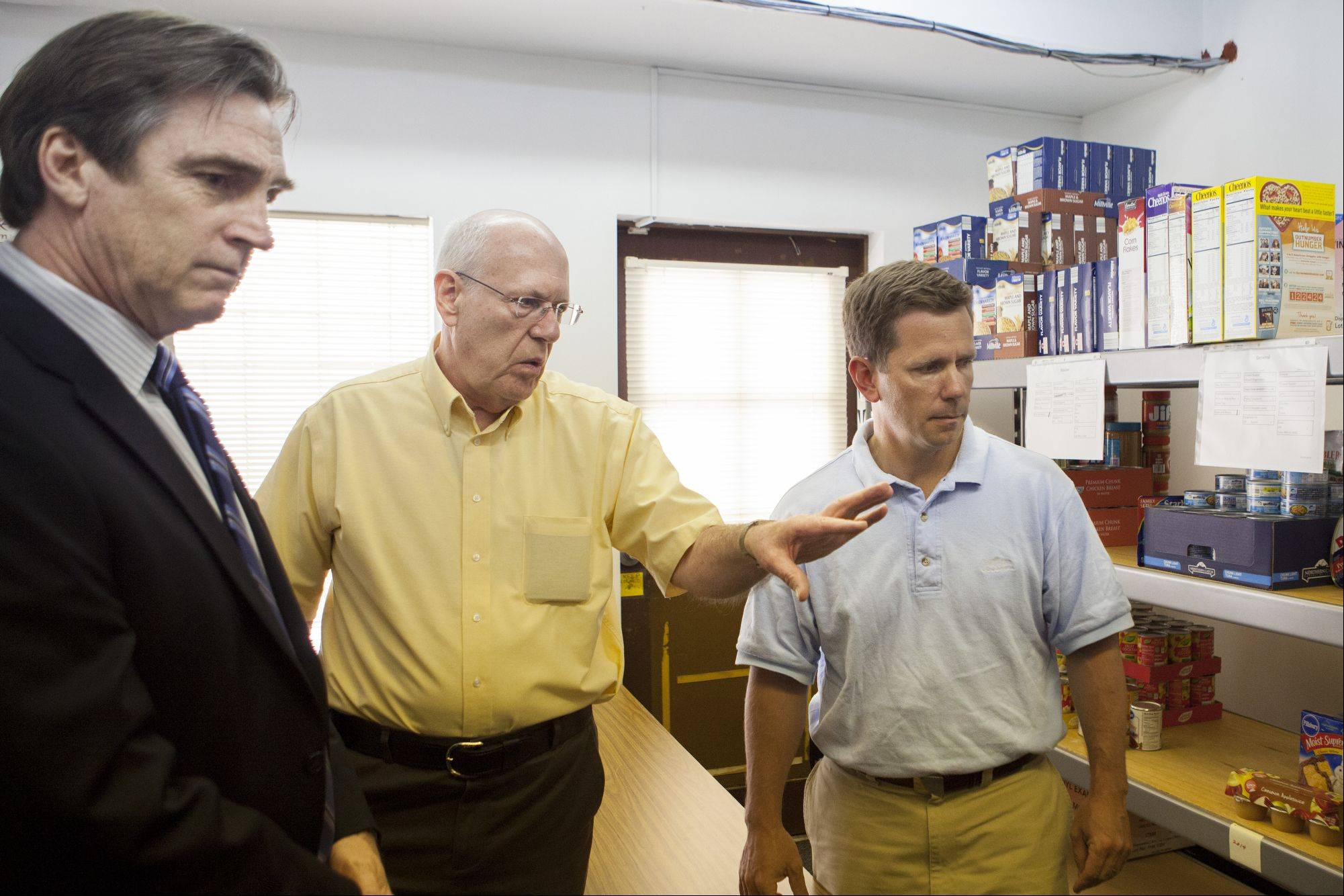 Jim Bradley talks to U.S. Rep Bob Dold and OMNI Youth Services Director Jay Meyer about the food in the Wheeling food pantry.