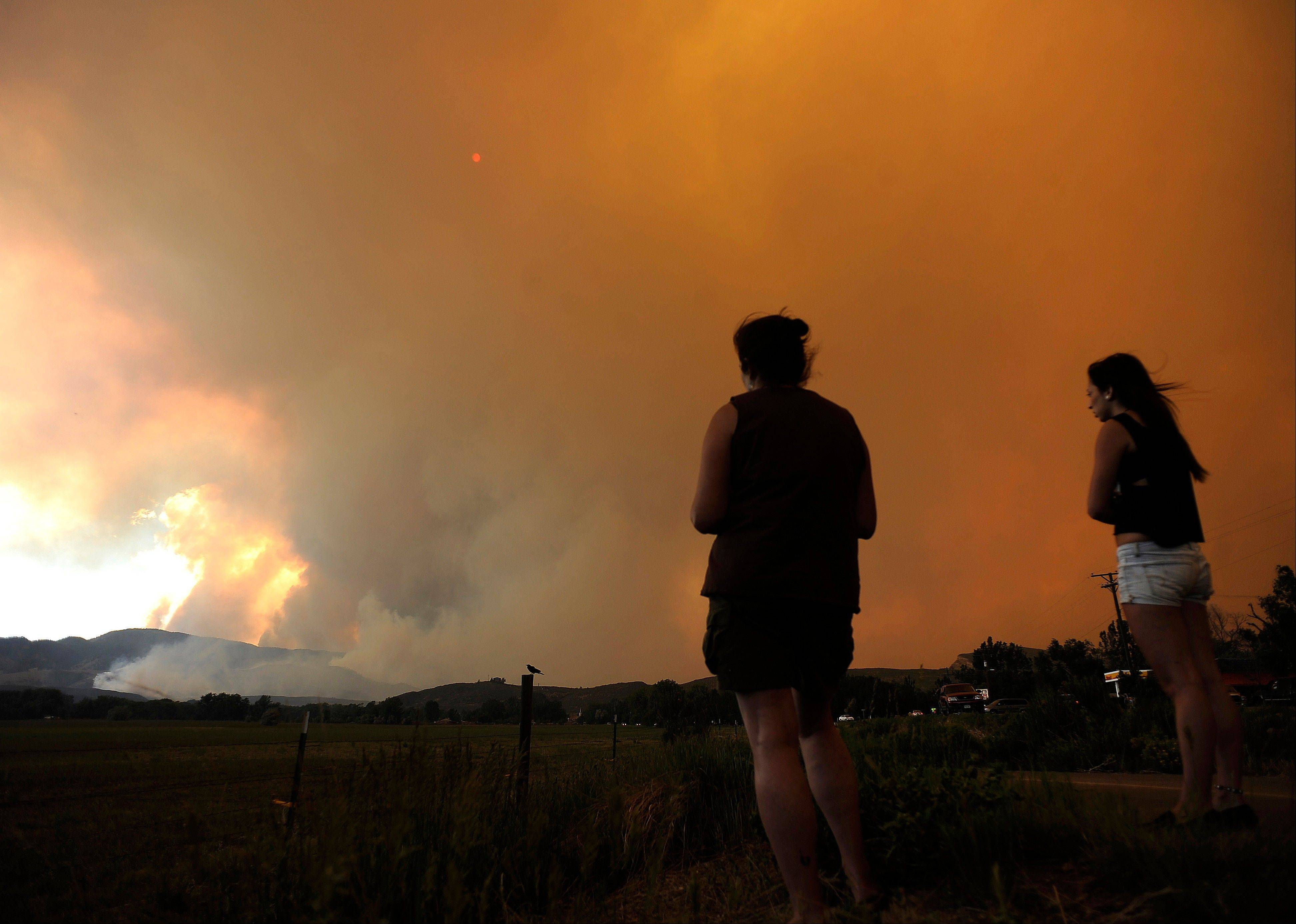 Donna Dundon, left, and Arianna Roupinian, of Fort Collins, Colo., watch a fire burning in a mountainous area about 15 miles west of Fort Collins, on Sunday, June 10, 2012. Firefighters on Sunday were fighting wildfires that have spread quickly in parched forests in Colorado and New Mexico, forcing hundreds of people from their homes and the evacuation of wolves from a sanctuary. The Colorado fire grew to 22 square miles within about a day of being reported and has destroyed or damaged 18 structures.