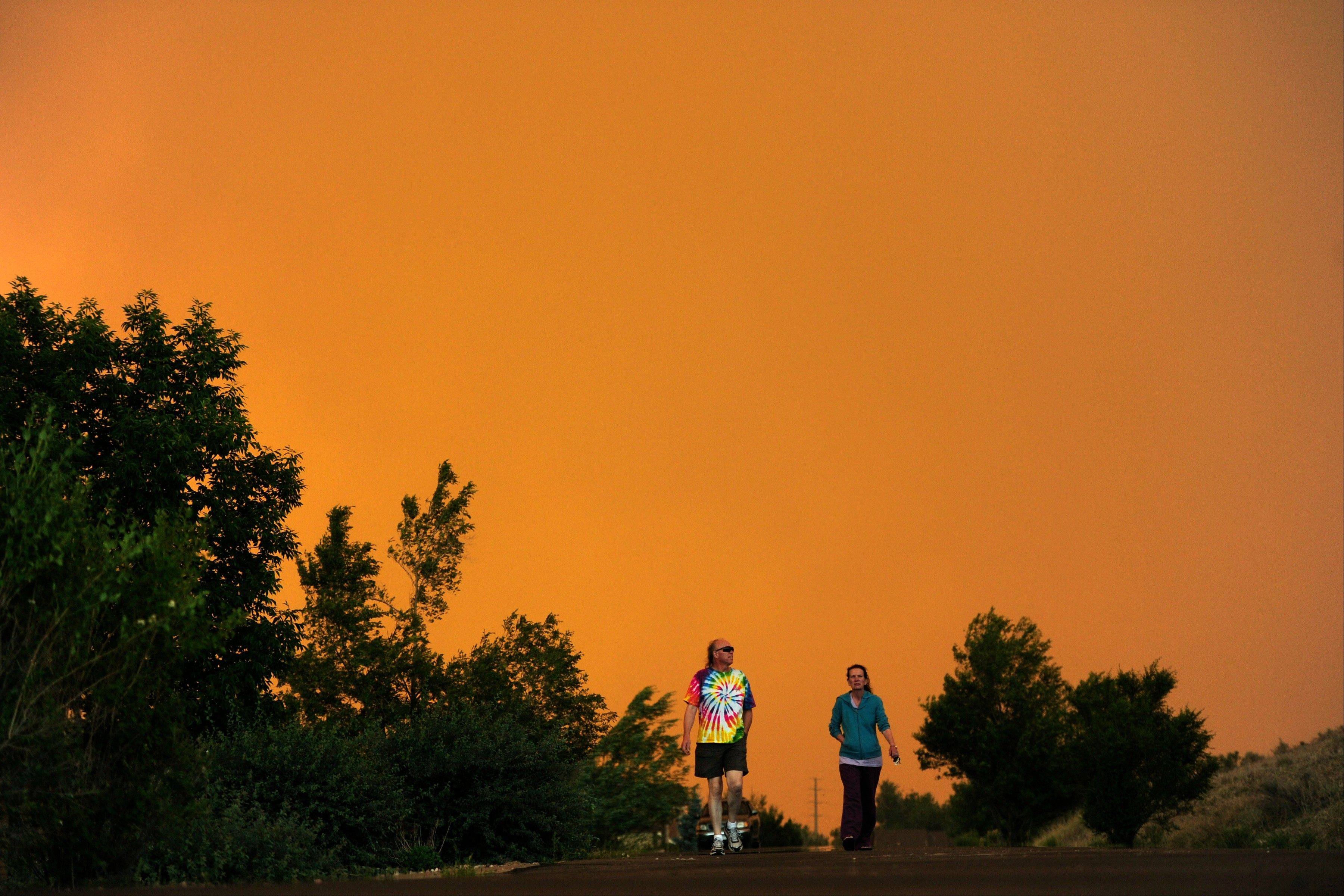 Diana and Donald Mangelsen walk near their home outside of LaPorte, Colo., as a wildfire burns in a mountainous area about 15 miles west of Fort Collins, Colo., on Sunday, June 10, 2012. Firefighters on Sunday were fighting wildfires that have spread quickly in parched forests in Colorado and New Mexico, forcing hundreds of people from their homes and the evacuation of wolves from a sanctuary. The Colorado fire grew to 22 square miles within about a day of being reported and has destroyed or damaged 18 structures.