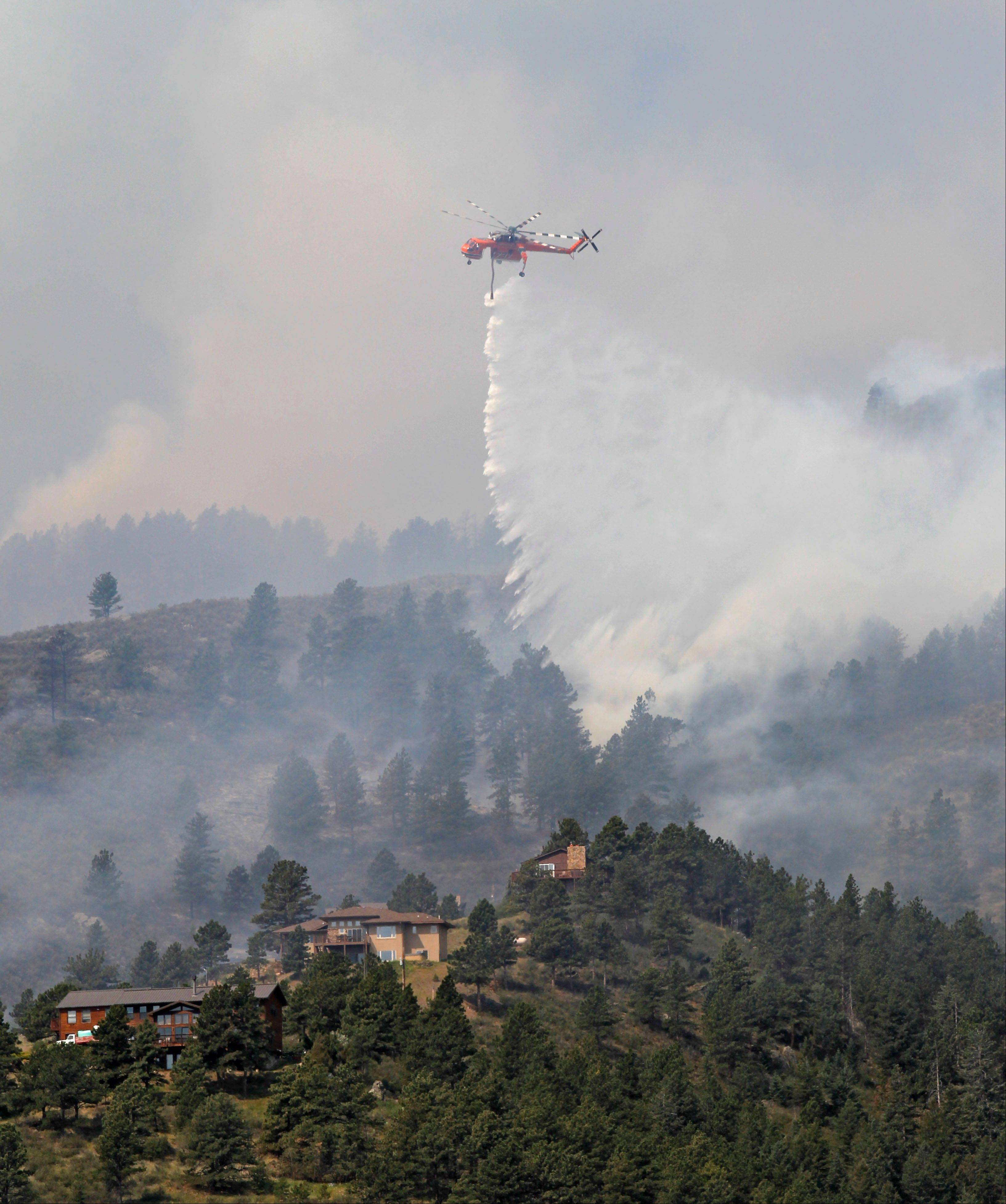 A helicopter drops water on trees burning behind homes on the High Park wildfire near Fort Collins, Colo., on Monday, June 11, 2012. The wildfire is burning out of control in northern Colorado, while an unchecked blaze choked a small community in southern New Mexico as authorities in both regions battled fires Monday.