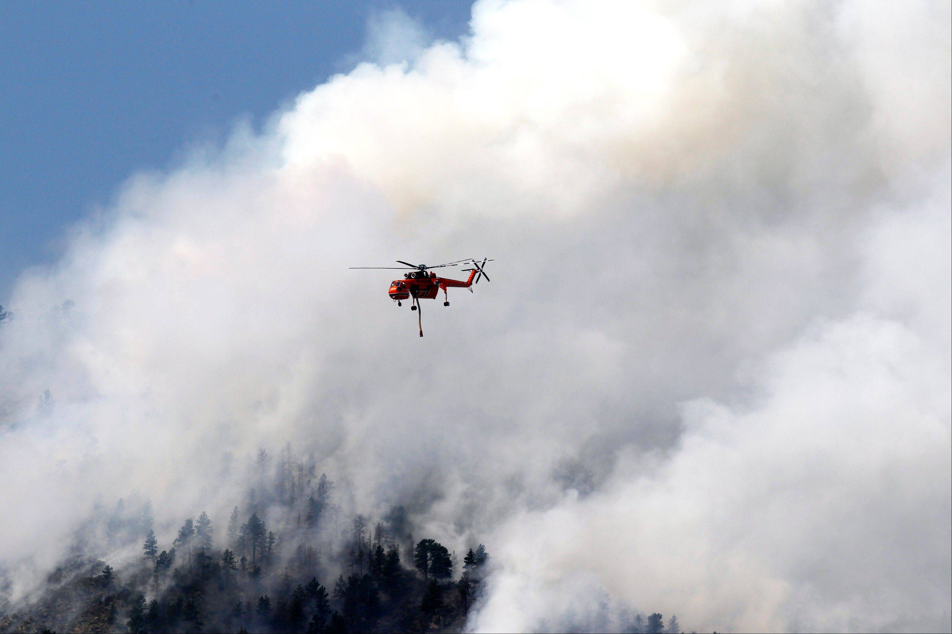 A helicopter flies through smoke after making a water drop on the High Park wildfire near Fort Collins, Colo., on Monday, June 11, 2012. The wildfire is burning out of control in northern Colorado, while an unchecked blaze choked a small community in southern New Mexico as authorities in both regions battled fires Monday.
