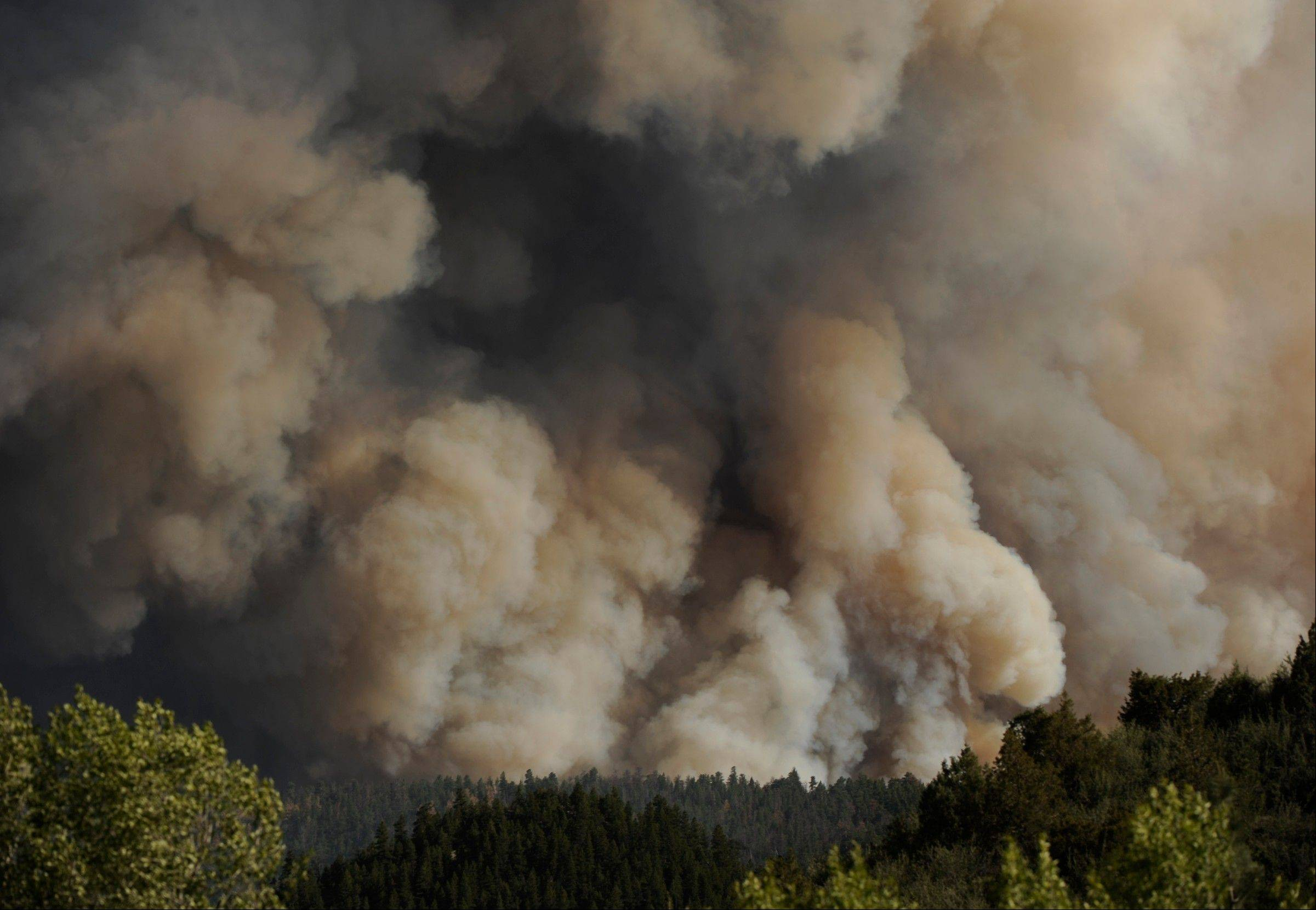 In this Saturday, June 9, 2012 photo, thick smoke rises from the burning fire south of the Cache La Poudre River at the intersection of Larimer County Road 27 and Colorado Highway 14, west of Fort Collins, Colo.
