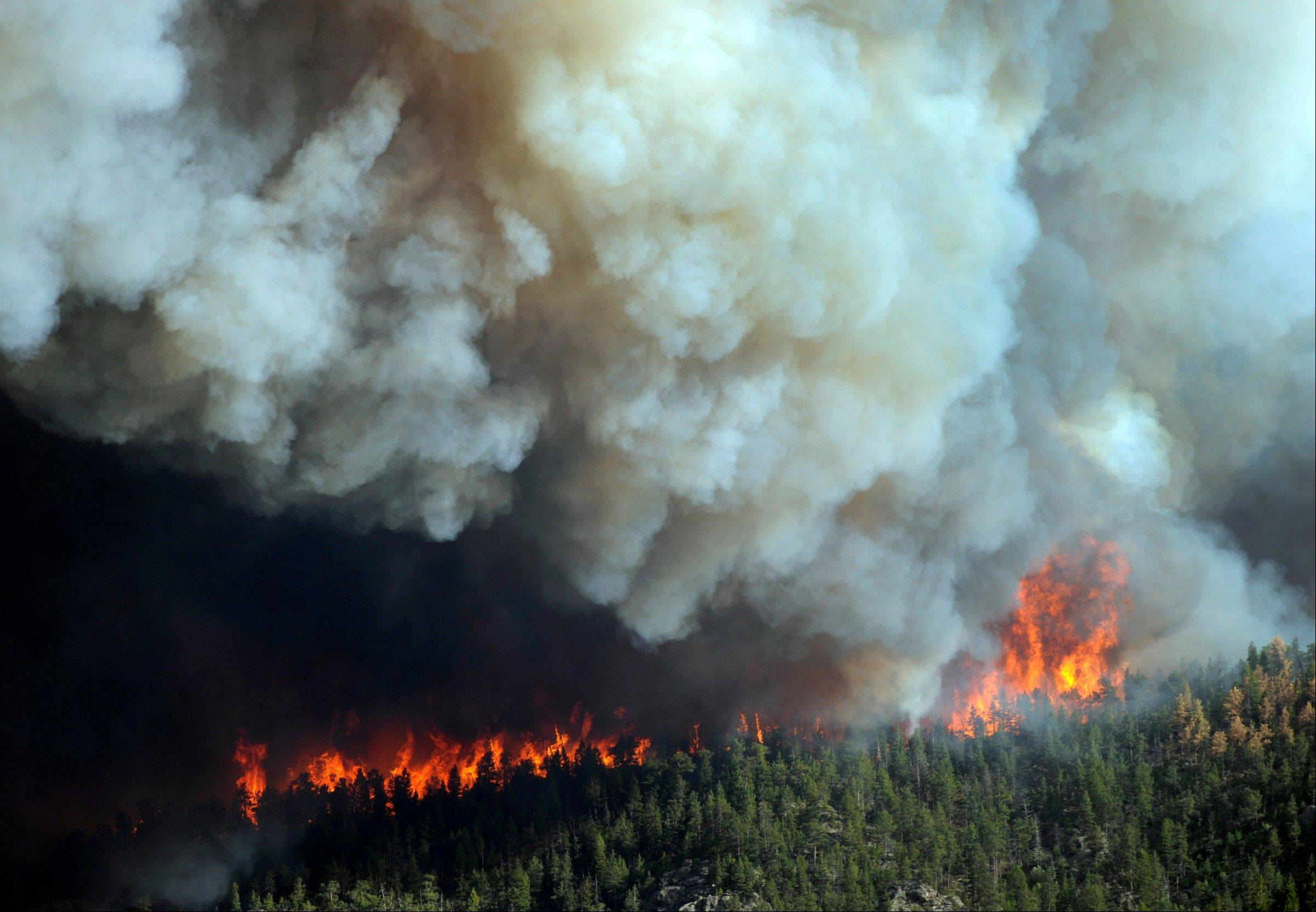 In this Saturday, June 9, 2012 photo, flames burn in the area near Larimer County Road 27 and Colorado Highway 14 of the High Park fire west of Fort Collins, Colo.