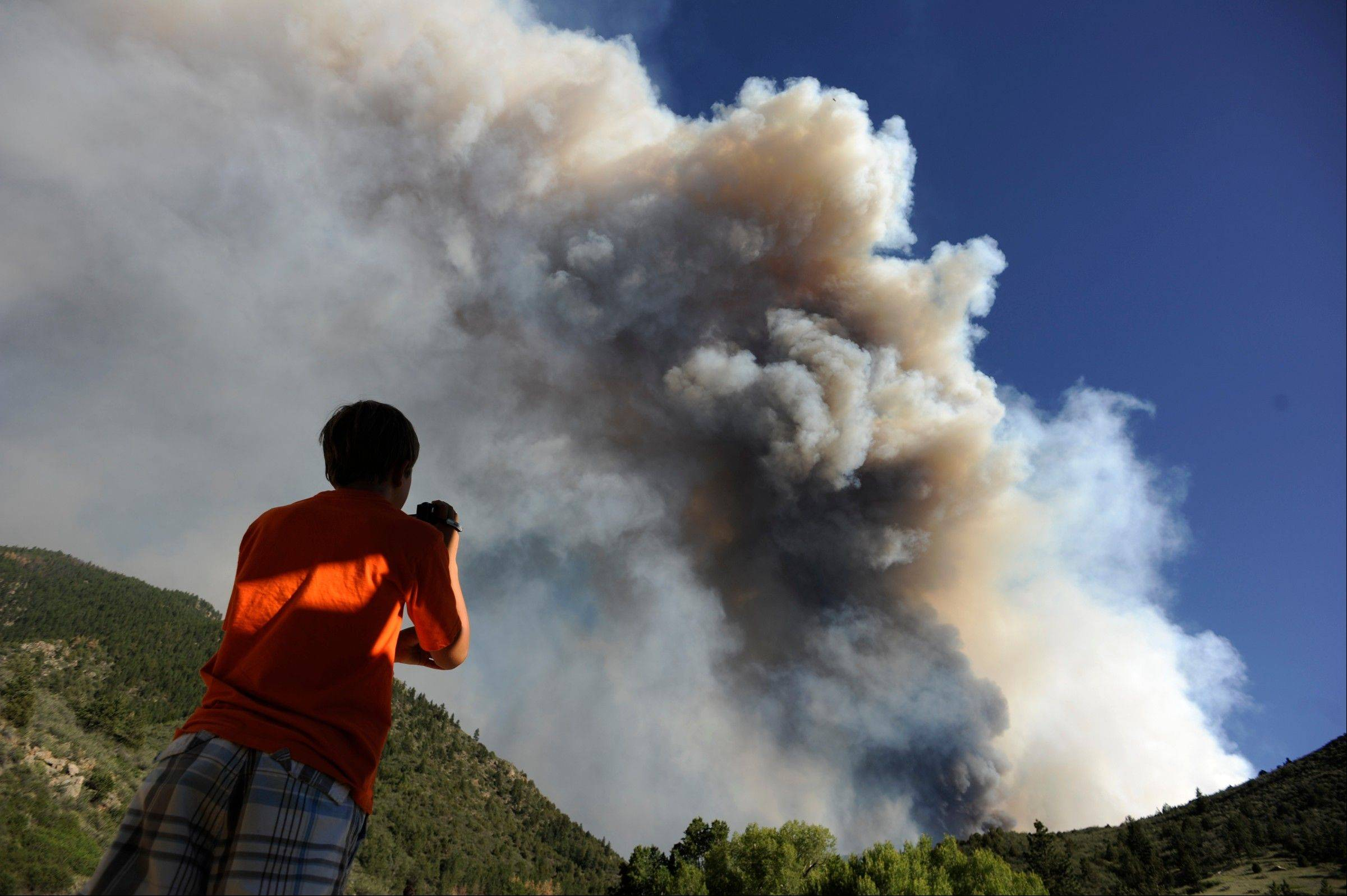 In this Saturday, June 9, 2012 photo, Zachary Brumley, 12, from Windsor, photographs a giant smoke plume as it rises above the flames as the fire crests a hillside south of the Cache La Poudre River at the intersection of Larimer County Road 27 and Colorado Highway 14, west of Fort Collins, Colo.