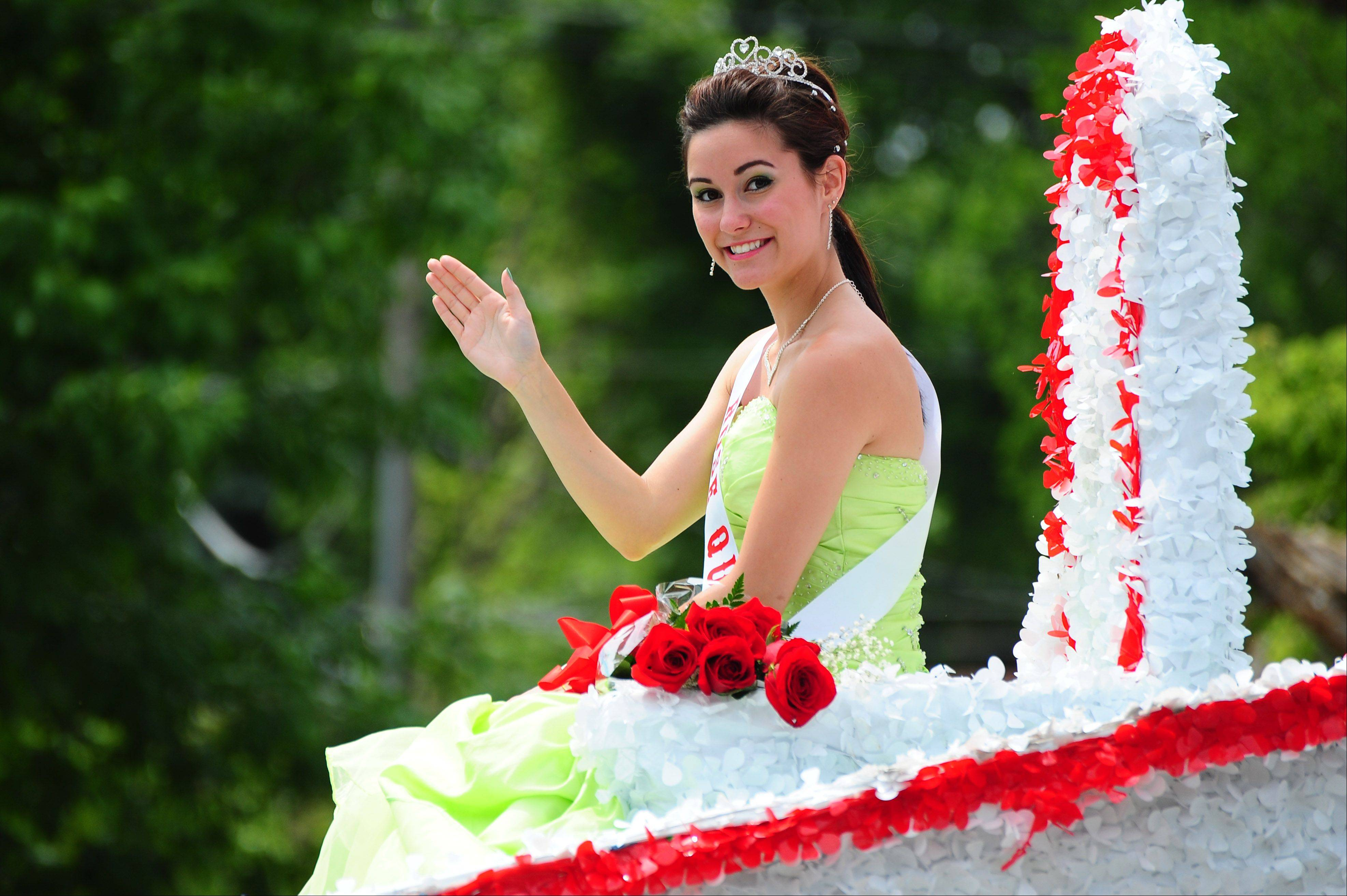 Roselle's Rose Queen, Lauren Caputo, waves at spectators as her float marches down Roselle Road during the annual Rose Parade on Sunday.
