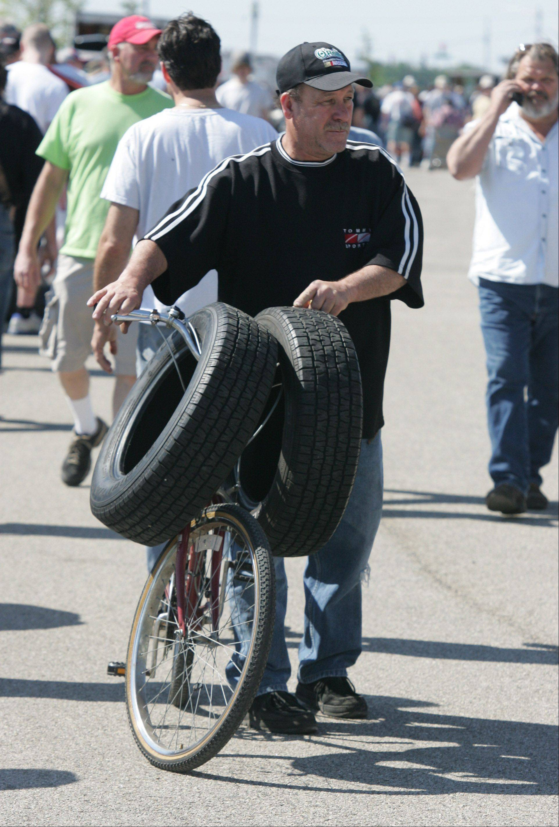 Manuel Torres, of Grayslake, walks with a bike and tires that he bought during Skip's Fiesta Drive-In Truck & Auto Swap Meet & Car Show Sunday at the Lake County Fairgrounds in Grayslake. The 30th anniversary celebration featured a parts swap meet and a display of antique and collectible automobiles.