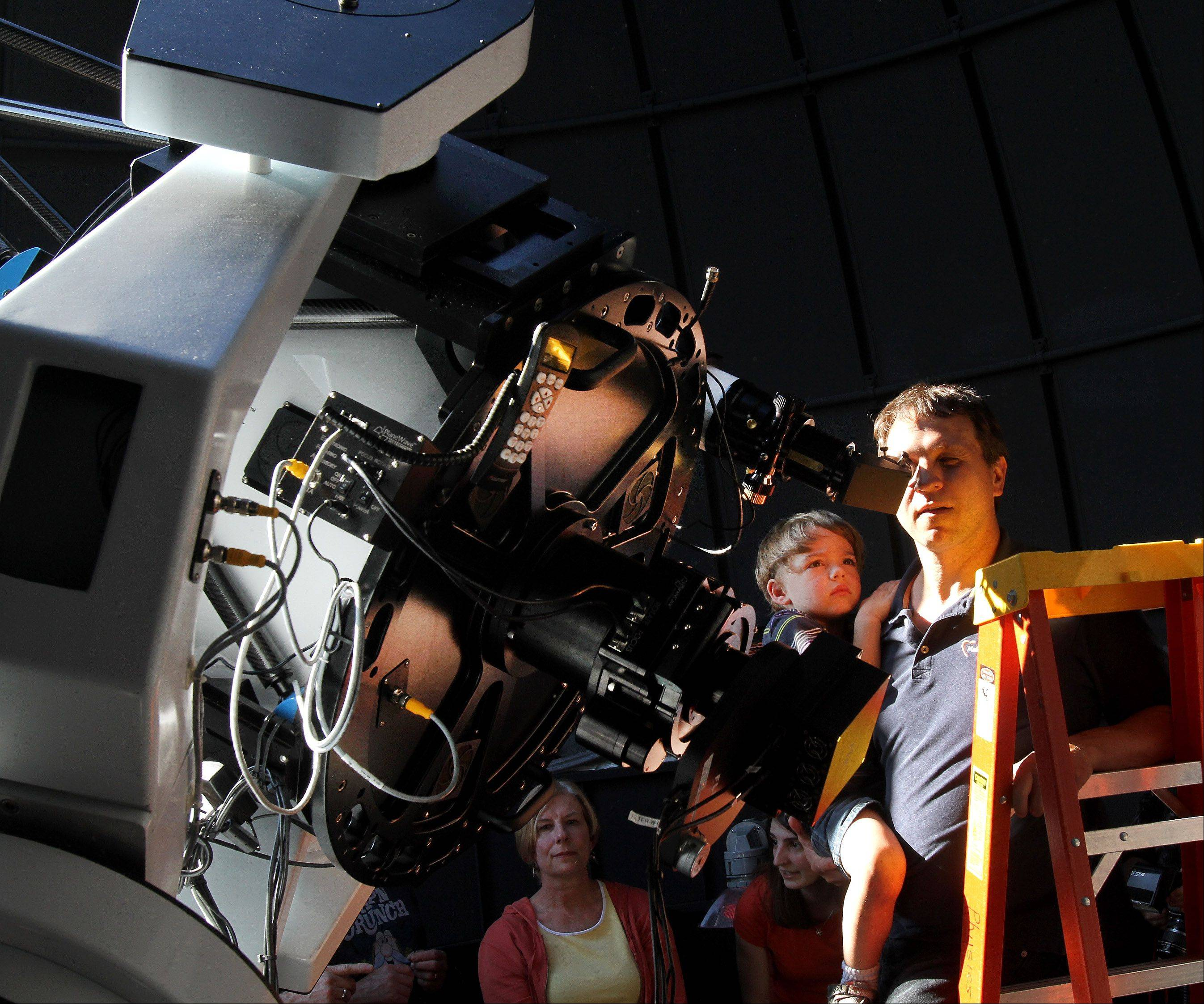 Andris Slokenbergs of Geneva and his son Emils, 3 1/2, take a look through the main telescope in the Wheaton College Astronomical Observatory, which opened Tuesday evening for free viewings of the Transit of Venus.