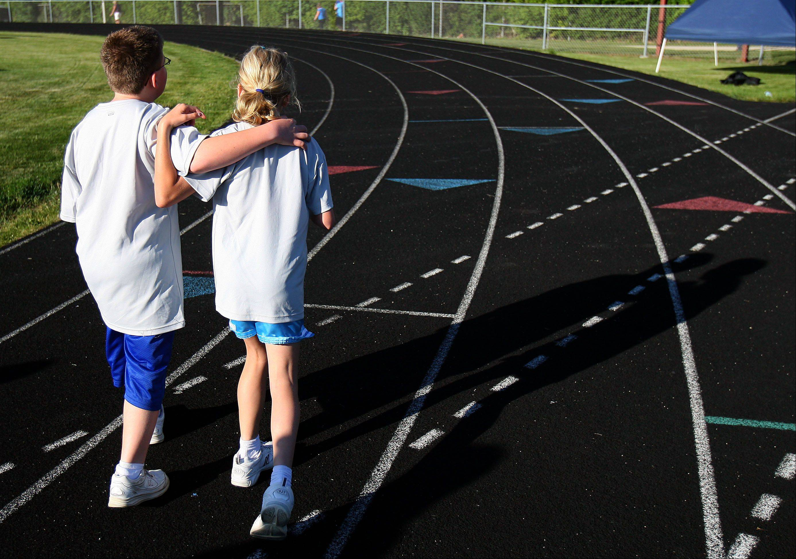 "11-year-old twins Alex and Amanda Malanick of Sugar Grove walk off the track after competing in the 200 meter dash during the 5th annual paralympic ""Run and Roll"" at McCracken Field in McHenry Wednesday. Children and teens up to age 21 with a primary physical or visual disability were encouraged to participate."