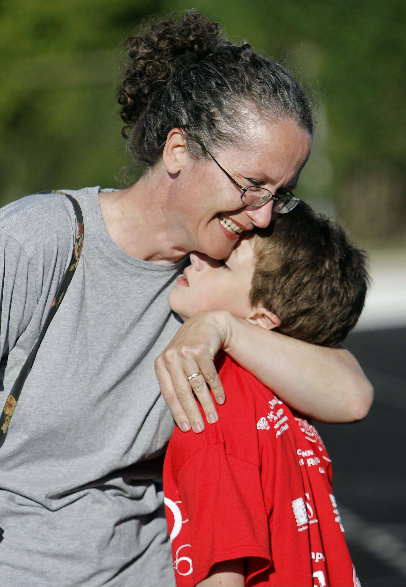 "Lisa Reiter of Cary hugs her 11-year-old son Sam after he competed in the 200 meter dash during the 5th annual paralympic ""Run and Roll"" at McCracken Field in McHenry Wednesday."