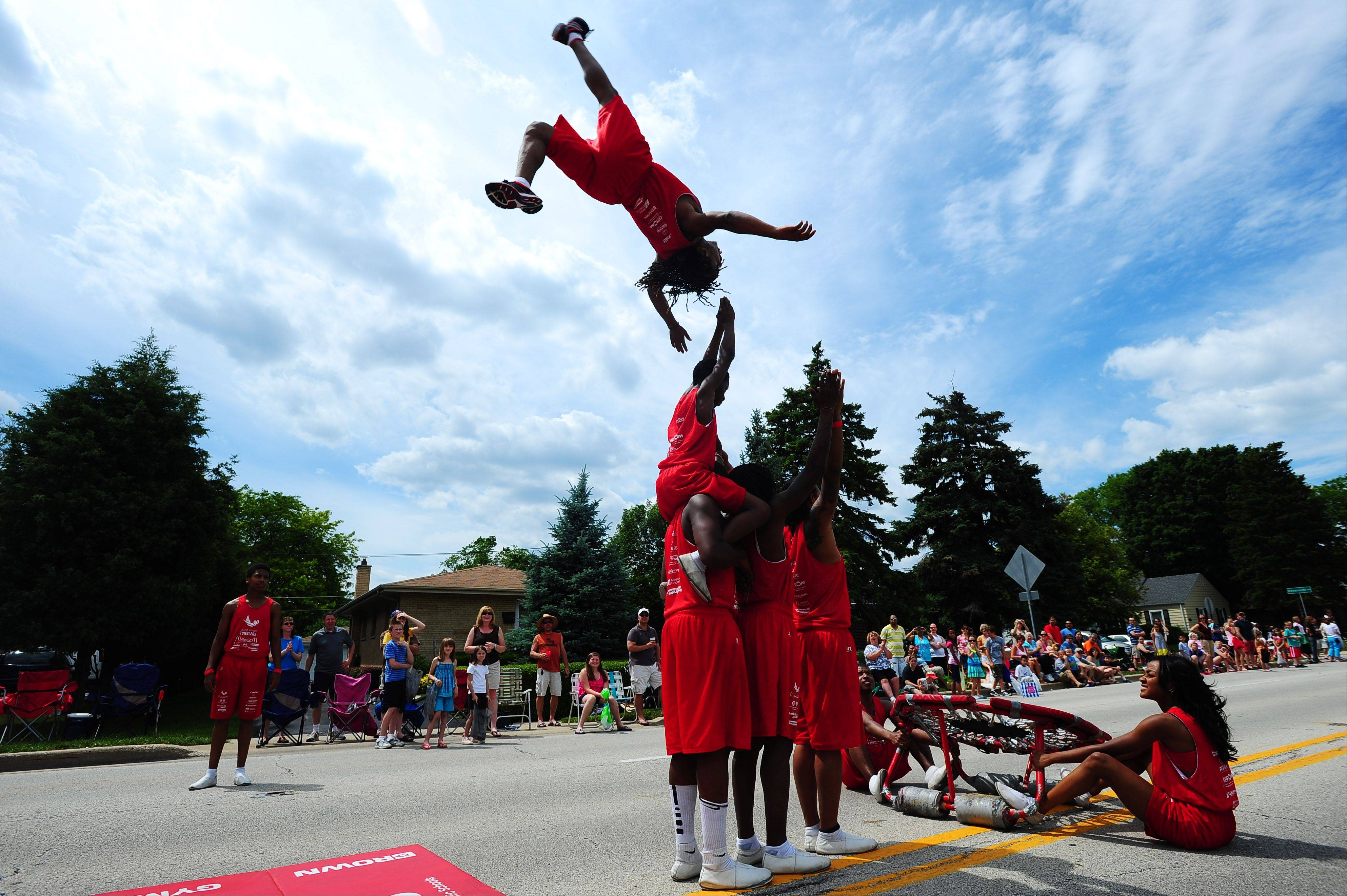 Members of the Jesse White Tumbling Team shock spectators with their acrobatic talents during the annual Rose Parade in Roselle on Sunday.