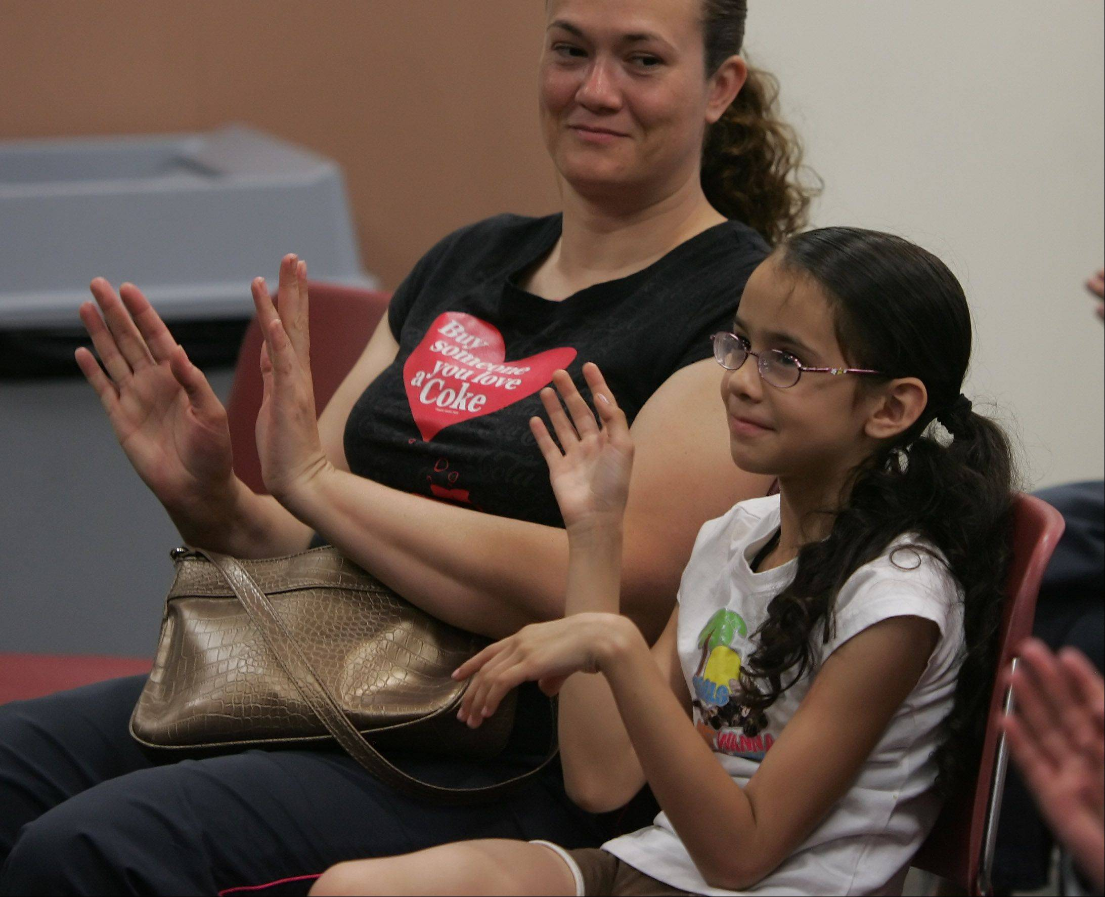Dania Ortiz, 8, of Round Lake Heights, and her mother, Alma, clap their hands to a song by Officer Ollie during the Puppet Crime Prevention program Monday by the Round Lake Police Department at the Round Lake Area Public Library. The puppets entertained and informed kids about stranger danger, getting lost, and the importance of knowing your address.