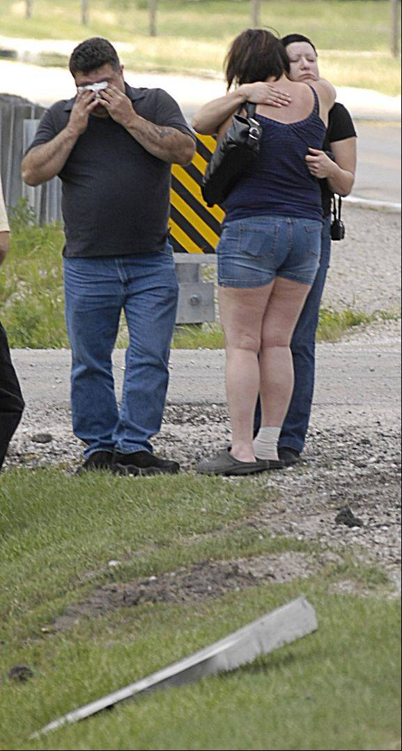 "Ricardo Banuelos wipes his eyes as his wife Raquel gets a hug from Anna Snitko, a neighbor of Brian Herrera who died along with their daughter Alexis and Tyler Montgomery in a triple fatal crash at Schlapp Road and Route 126 in rural Kendall County, Tuesday. Ricardo Banuelos said of his daughter ""she was full of life and lived life to the fullest""."