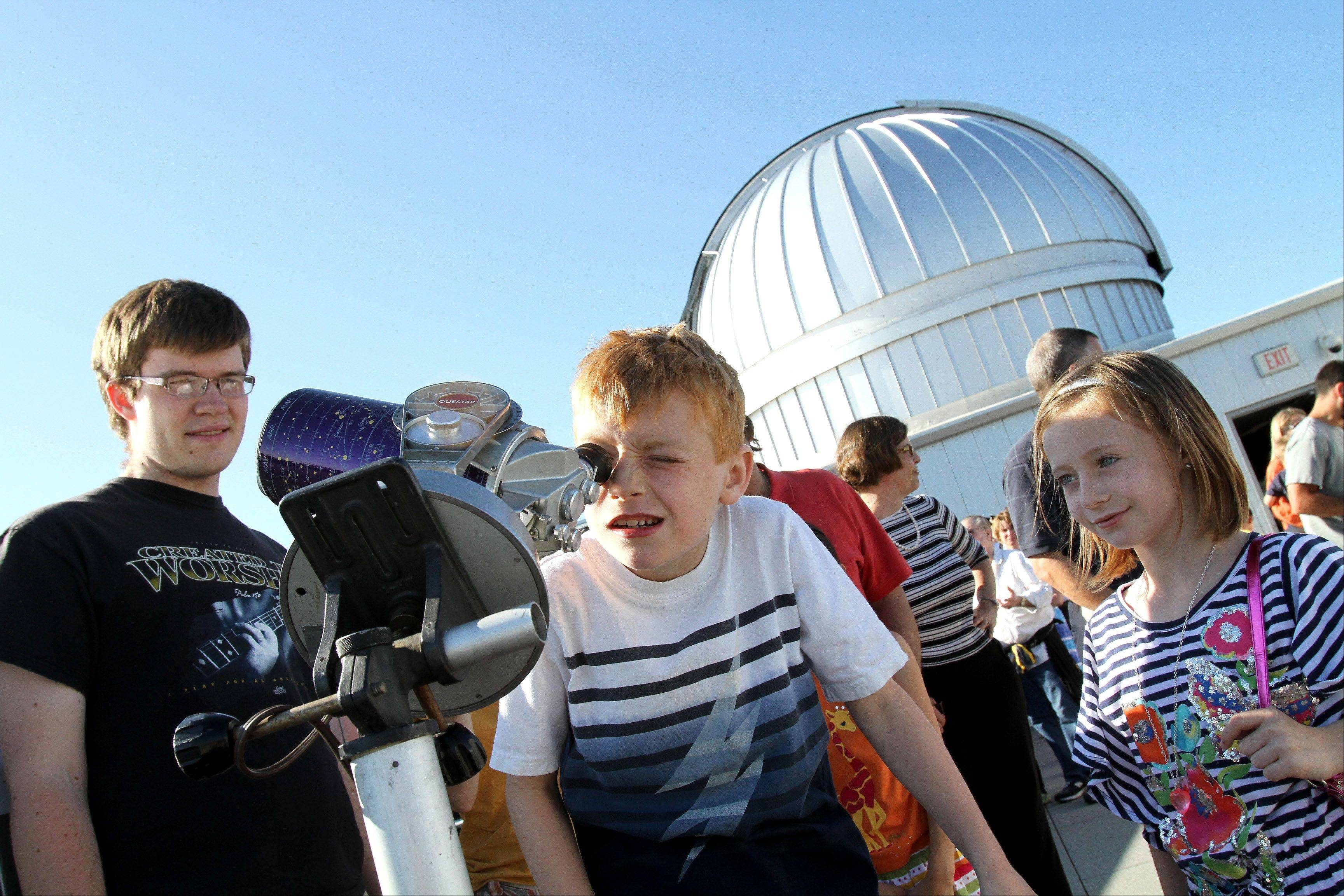 Sam Gibbons, 8, of Lombard, takes a look through a smaller telescope on the roof of the Wheaton College Astronomical Observatory, which opened Tuesday evening for free viewings of the Transit of Venus. On the right is Sam's sister Gracie, 10 and on the left is student Daniel Flavin, helping out with the event. Hundreds of people lined up to look through several different telescopes.
