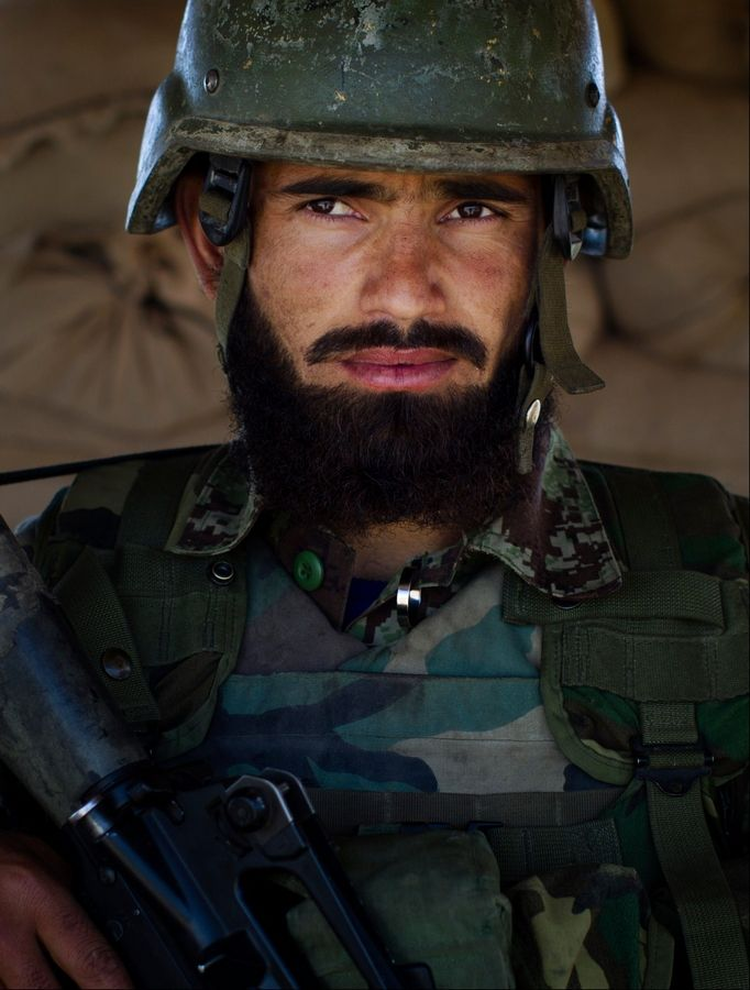"Afghan National Army soldier Noor Alam, 25, poses Tuesday for a picture at the Chinari outpost in Logar province, east Afghanistan, wearing his unit's single helmet. Alam is from Afghanistan's eastern Nangarhar province, where the vast majority are ethnic Pashtuns, the same as most Taliban. He recalls scary encounters with the Taliban in his four years in the army but none as frightening as the one with U.S. Special Forces who he says mistook his base for a Taliban hideout. ""Their weapons were so strong. I have had bad experiences with the Taliban but this was the most frightening for me,"" he said. ""Maybe they apologized to higher-ups, but no one apologized to us."" He said he longs for ""peace with all Afghans, living together. We shouldn't fight each other."""