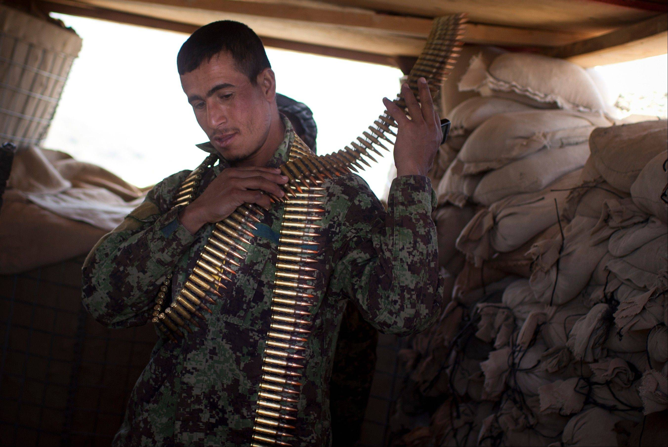 An Afghan National Army soldier puts on a bandoleer of bullets at his position at Chinari outpost in Logar province, east Afghanistan, on Tuesday. The months-old outpost was built after a police post at the base of the hill was attacked and destroyed by Taliban forces.