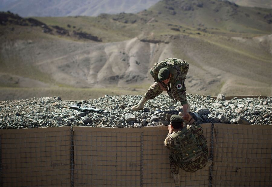 An Afghan National Army soldier helps his comrade to get onto his position at Chinari outpost in Logar province, east Afghanistan, on Tuesday. The months-old outpost was built after a police post at the base of the hill was attacked and destroyed by Taliban forces.