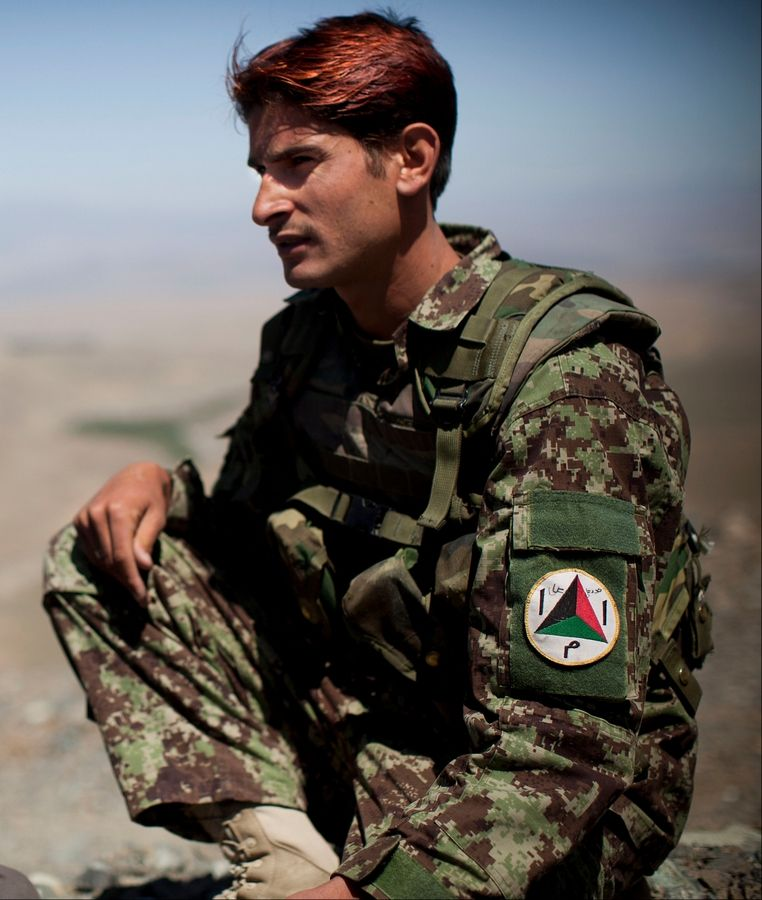 "Afghan National Army soldier Noor Ali, 21, poses Tuesday for a picture at the Chinari outpost in Logar province, east Afghanistan. Ali thinks he's 21, lost his parents when he was young, never went to school, worked as a laborer. He joined the army 10 months earlier and learned basic reading and writing. He dyed his hair flaming red, explaining shyly, ""I did this to look good. In my village it is popular."""