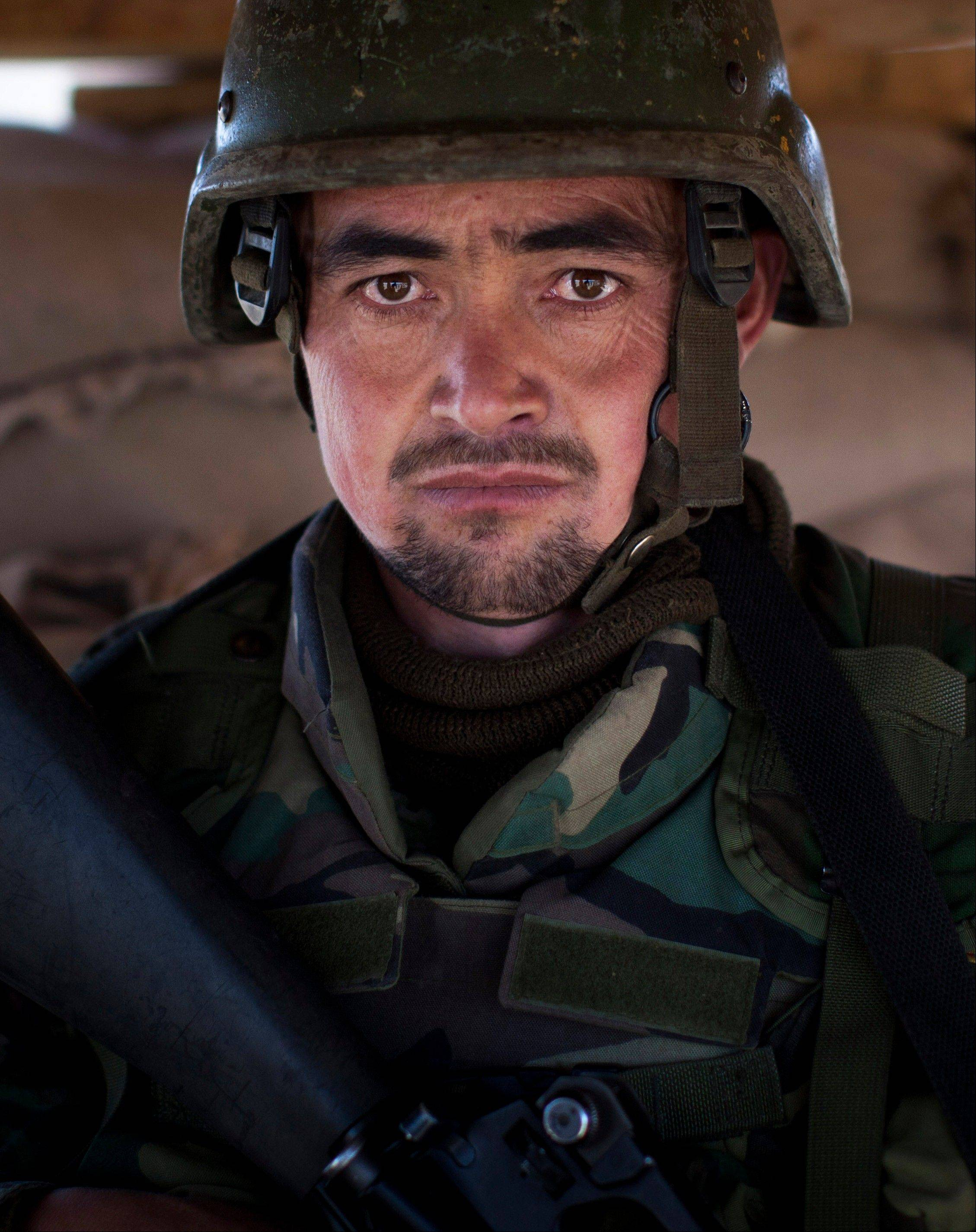 "Afghan National Army soldier Sgt. Abdul Bashir, 23, poses Tuesday for a picture at the Chinari outpost in Logar province, east Afghanistan, wearing his unit's single helmet. At 23, Bashir is a veteran. One of 15 children, he joined up four years ago ""to serve my country."" He accuses Iran and Pakistan of interfering in his troubled homeland but believes Afghanistan will have a better chance at peace after international forces leave. He longs for ""a country that is peaceful and can develop and where a soldier all alone can go anywhere in the country without feeling any danger."""