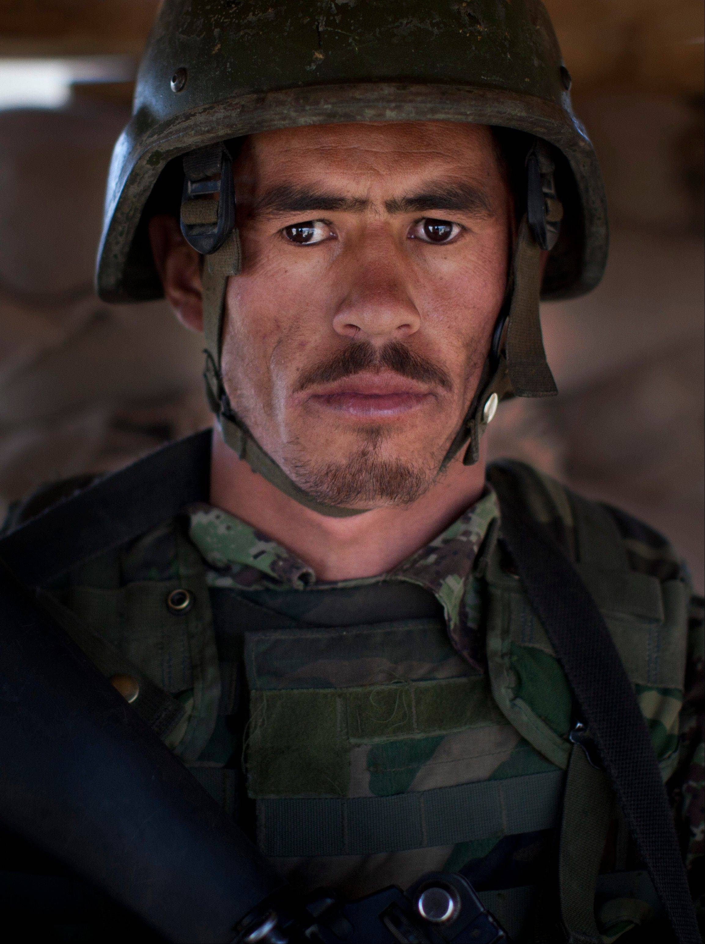 "Afghan National Army soldier Mohammed Khan, 21, poses Tuesday for a picture at the Chinari outpost in Logar province, east Afghanistan, wearing his unit's single helmet. At 21, his face is weathered and lined making him look older than his years. Khan is a new recruit from Afghanistan's northern Baghlan province and the only son of an elderly father who can no longer work. He says the Afghan National Army can defend the country after 2014 -- ""I have trust and belief in the ANA"" -- and thinks Afghanistan will be better off once the foreign forces are gone ""because when they are gone, we will be more able to control our country."" He hasn't yet been under fire but said: ""I am not afraid of the Taliban. I am only afraid of God."""