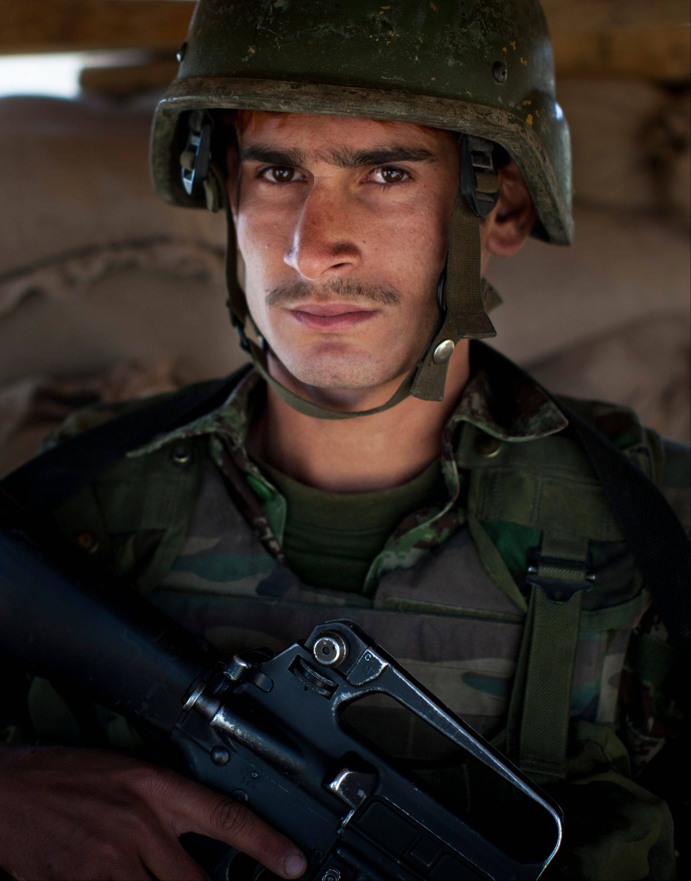 "Afghan National Army soldier Noor Ali, 21, poses for a picture Tuesday at the Chinari outpost in Logar province, east Afghanistan, wearing his unit's single helmet. Ali thinks he's 21, lost his parents when he was young, never went to school and worked as a laborer. He joined the army 10 months ago and learned basic reading and writing. He dyed his hair flaming red, explaining shyly, ""I did this to look good. In my village it is popular."""