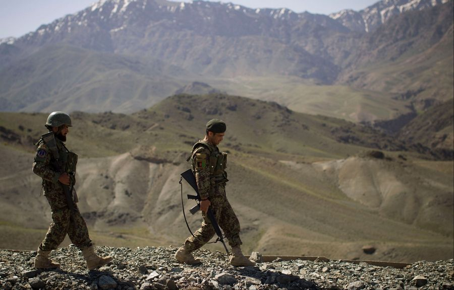 Afghan National Army soldiers walk to their position at Chinari outpost in Logar province, east Afghanistan, on Tuesday. The months-old outpost was built after a police post at the base of the hill was attacked and destroyed by Taliban forces.