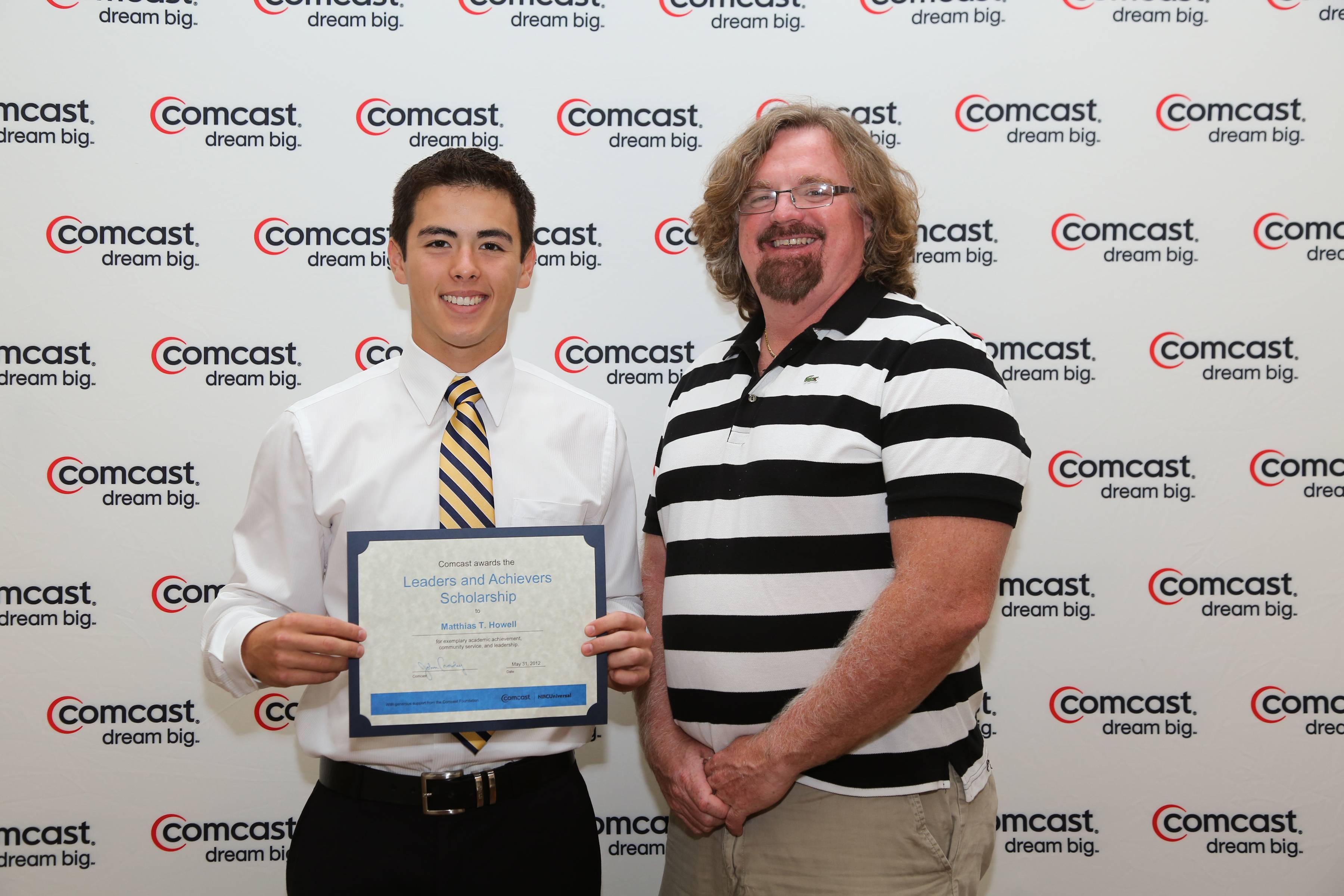 Matthias Howell accepts a $1,000 Comcast Leaders and Achievers Scholarship