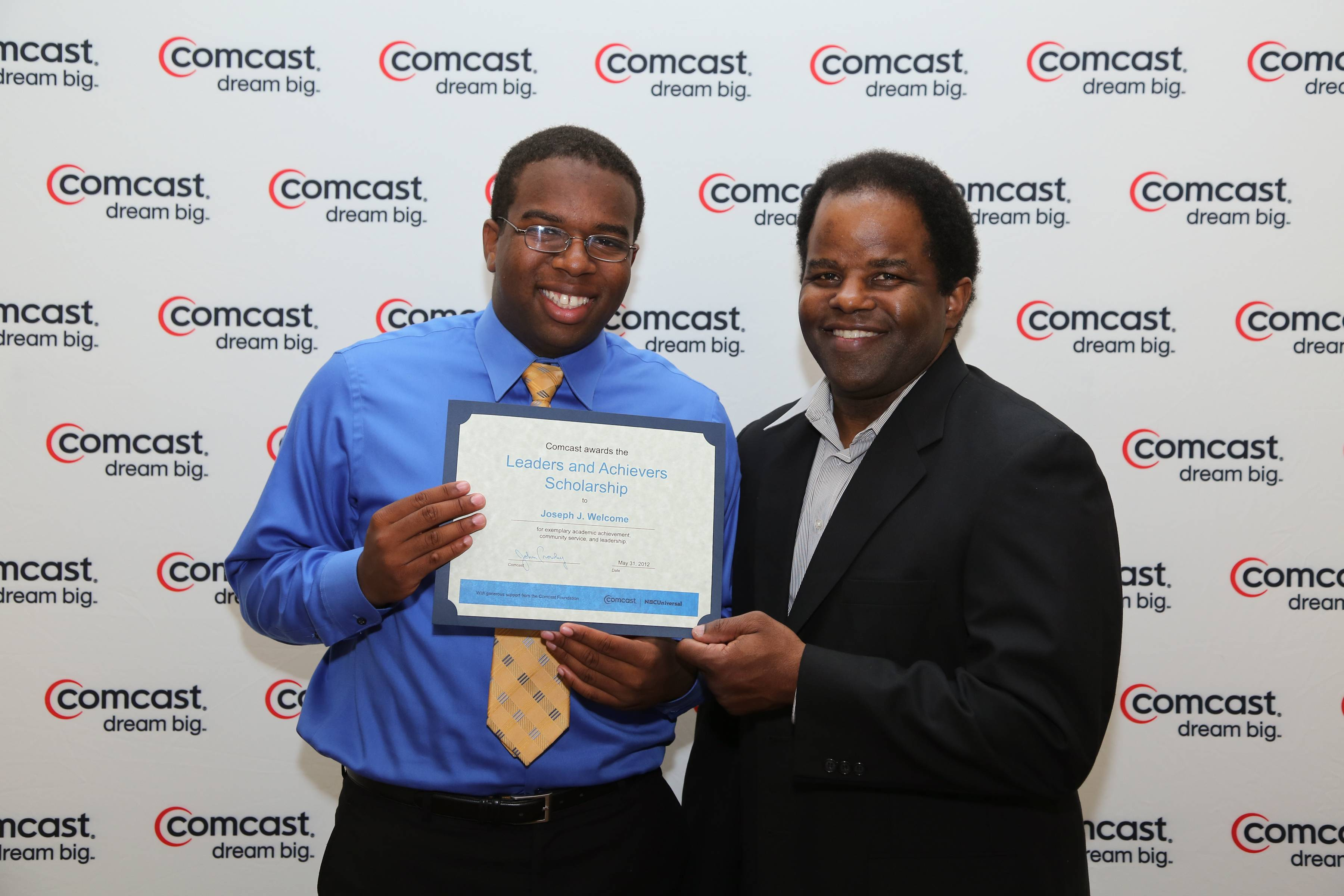 Joseph Welcome accepts a $1,000 Comcast Leaders and Achievers Scholarship