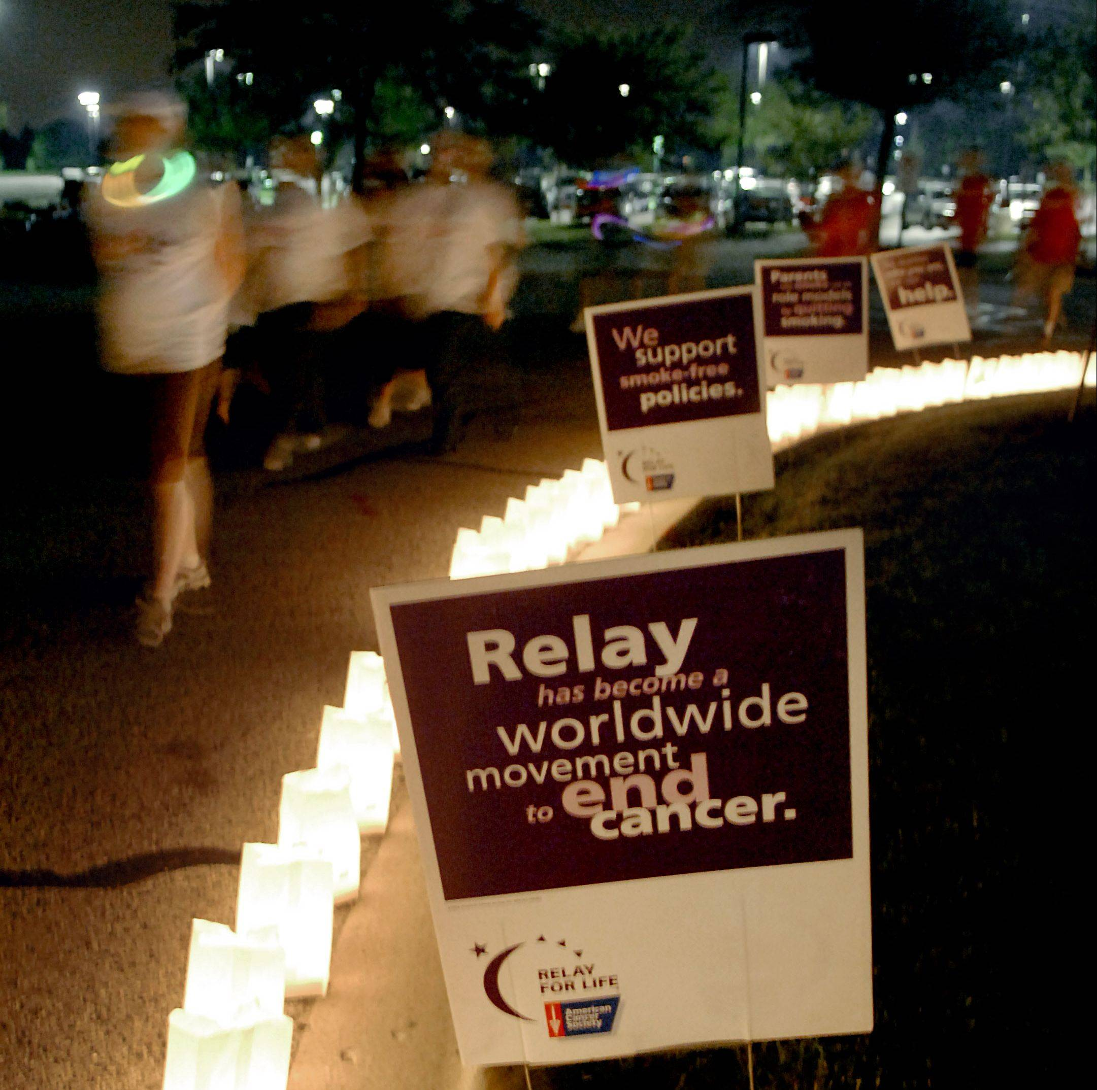 Walkers circle a line of luminarias at Elgin Community College's Relay For Life last month. Each year, local Relay For Life events in the suburbs raise thousands of dollars for the fight against cancer.