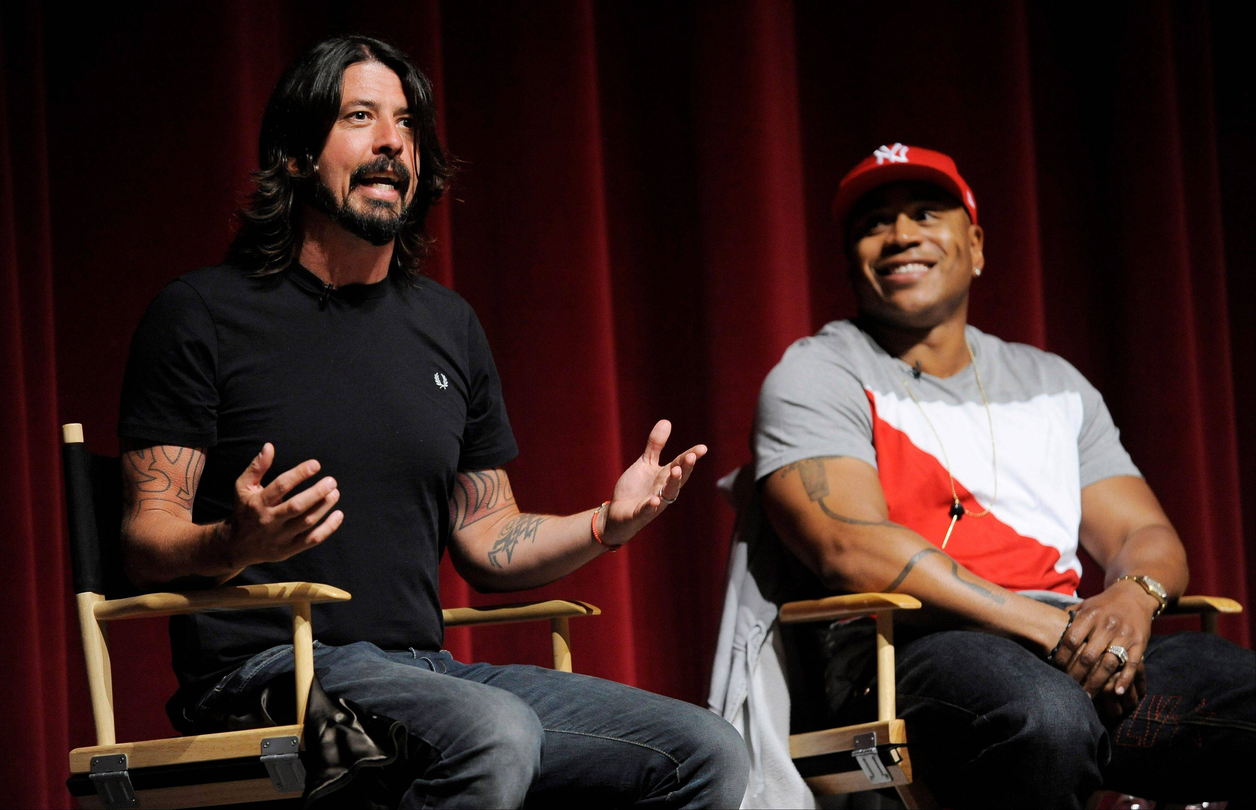 "Musicians Dave Grohl, left, and LL Cool J take part in a panel discussion following the premiere of the documentary film ""A Death in the Family: The Show Must Go On,"" at the Leonard H. Goldenson Theatre in Los Angeles Monday. The film features rare behind-the-scenes footage from this year's 54th Annual Grammy Awards."