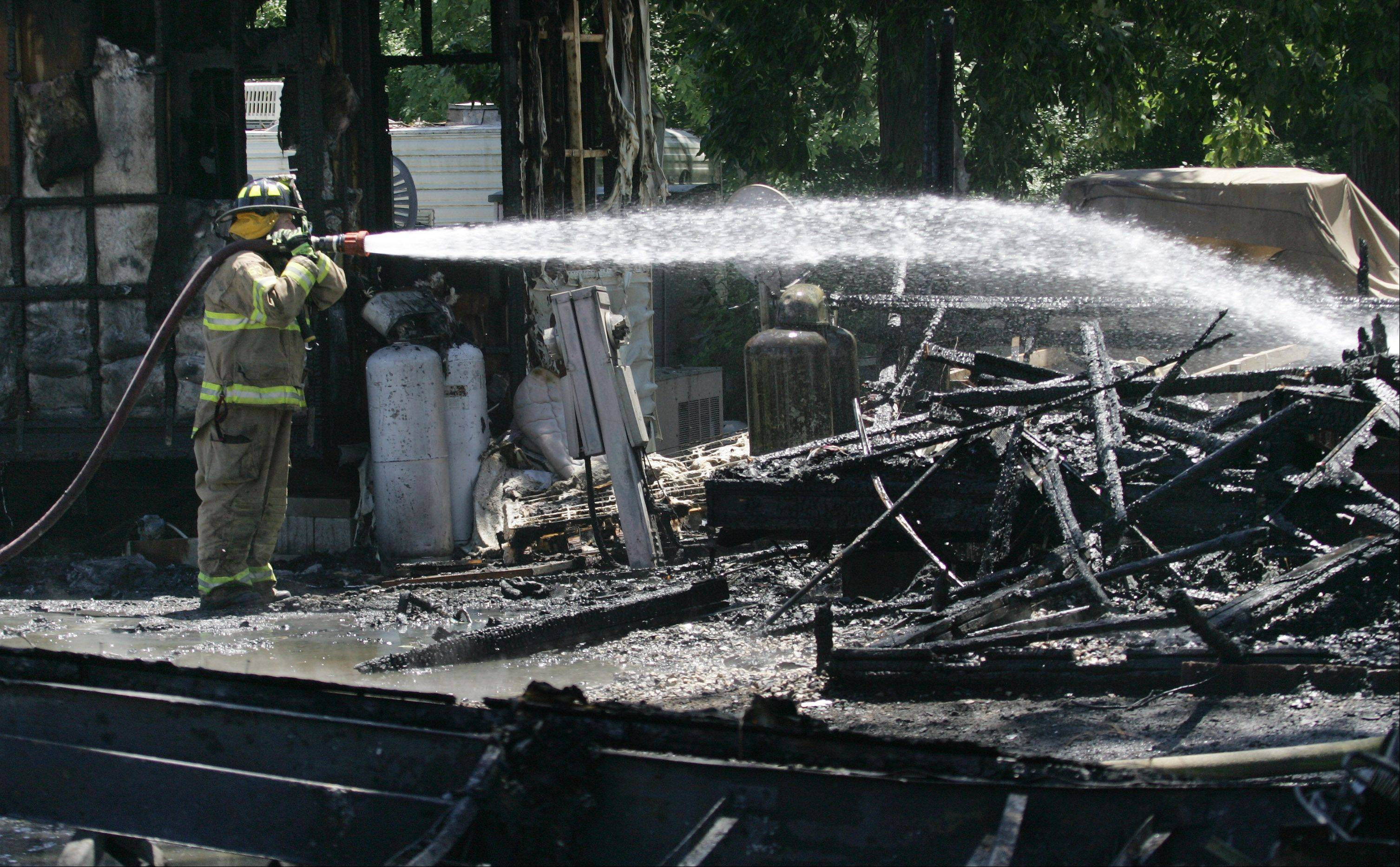 Gilbert R. Boucher II / gboucher@dailyherald.comAn Antioch firefighter sprays waters on the remains of one mobile home as he joined other Lake County firefighters battling a fire involving multiple mobile homes in Grass Lake Marina & R.V. Park Tuesday near Antioch. Fire departments from Antioch, Lake Villa, Fox Lake and Gurnee assisted in the multiple alarm fire.