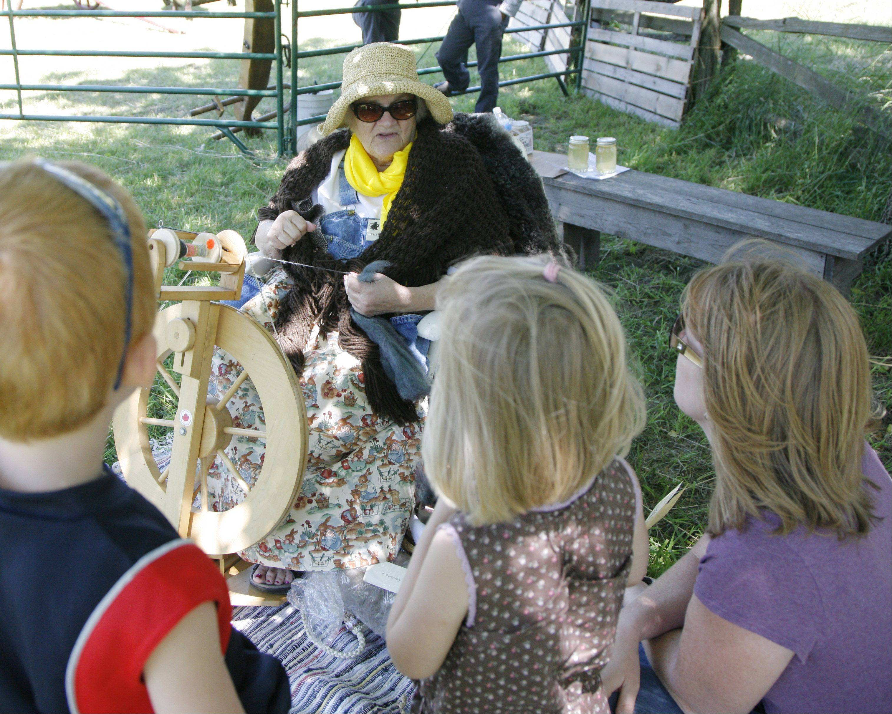 Elizabeth Cherry from rural Oswego shows a group of Batavia residents how to make spools of yarn from wool during a previous 1840s Days at Garfield Farm Museum.