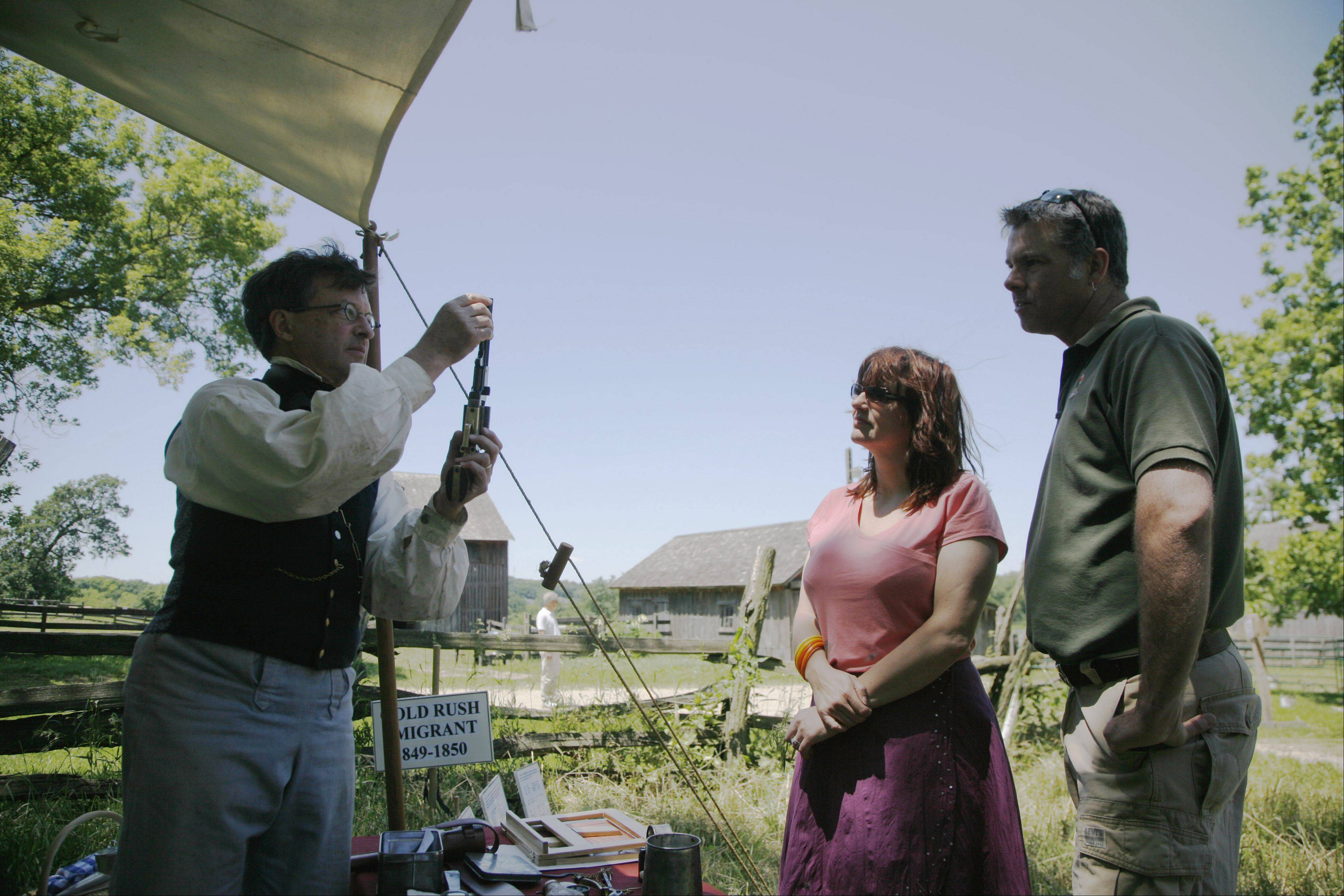 Keith Ryder of Wheaton shows an old revolver to Batavia residents Catherine and Ross Bennett during a previous 1840s Days event at Garfield Farm Museum.