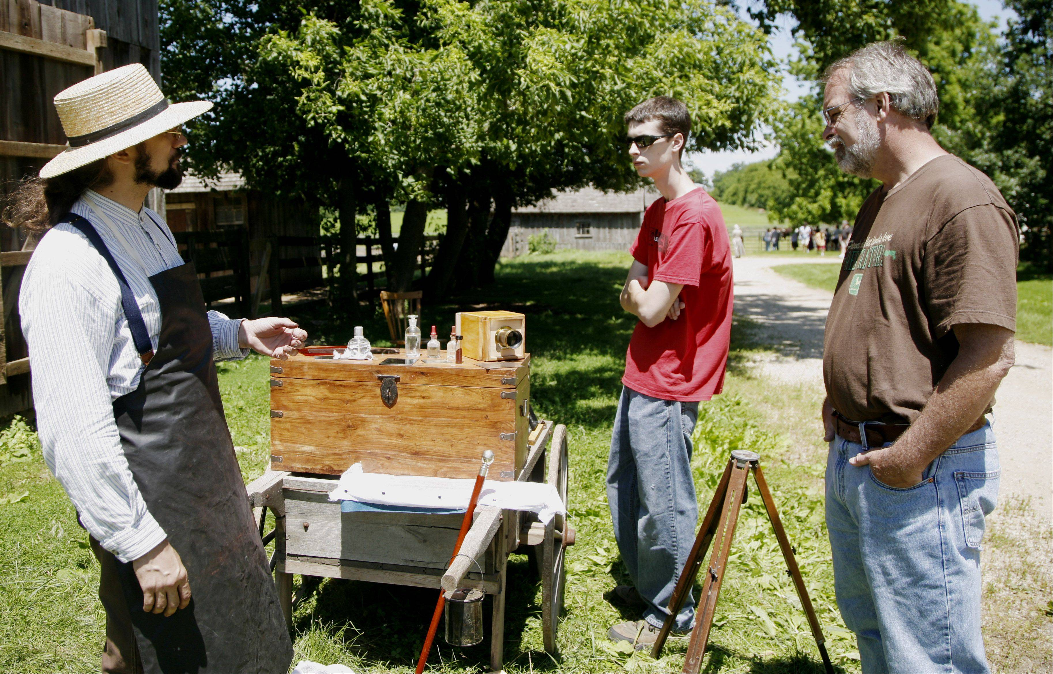 Chris Olsen of Campton Hills demonstrates a daguerreotype camera to Lisle residents Rick Fischer and his son Rick during a previous 1840s Days at Garfield Farm Museum.