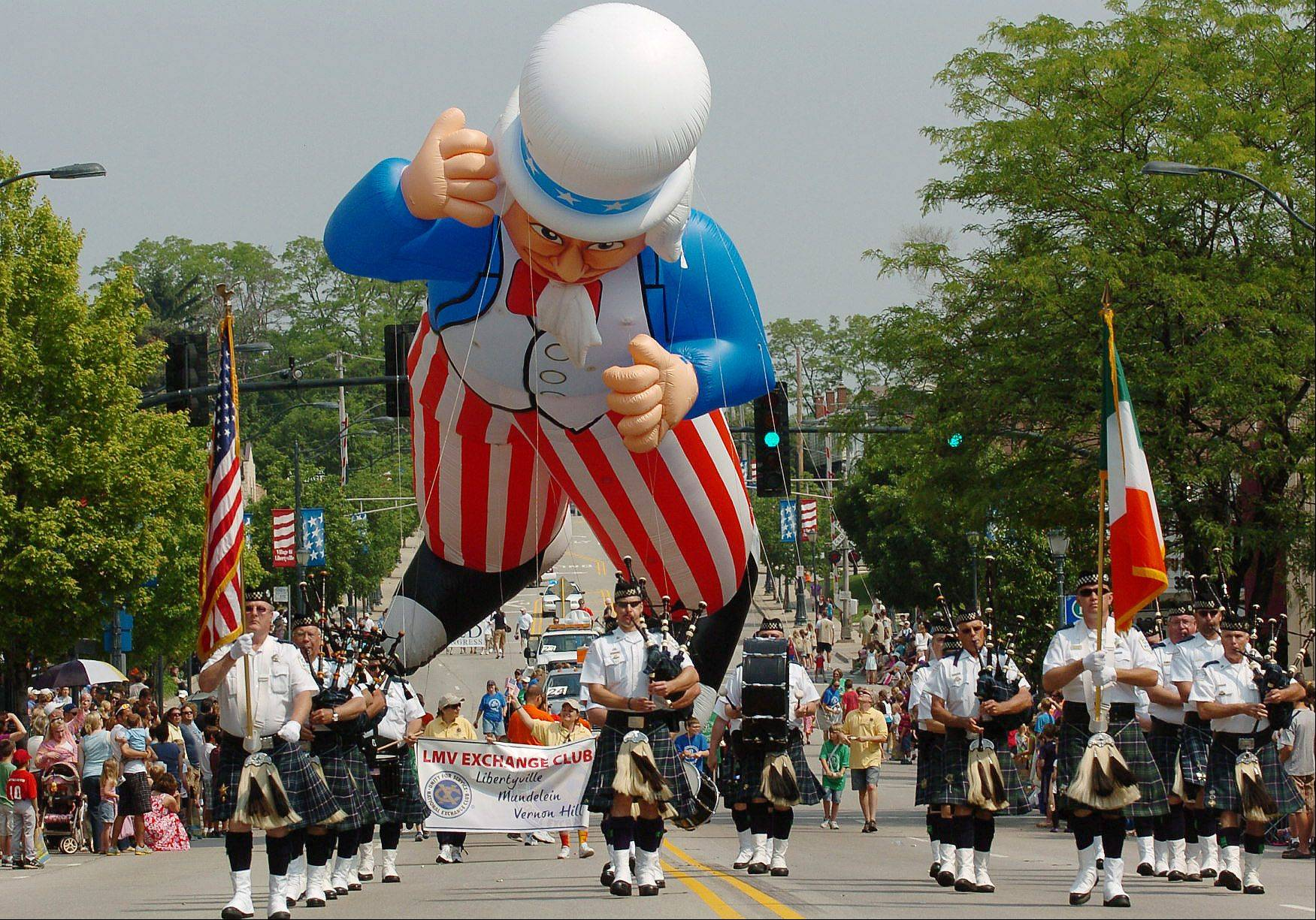 A giant floating Uncle Sam makes its way down Milwaukee Avenue during Libertyville Days parade last year. A worldwide helium shortage means parade viewers this year will see only a few of the giant balloons, a traditional highlight of the event.