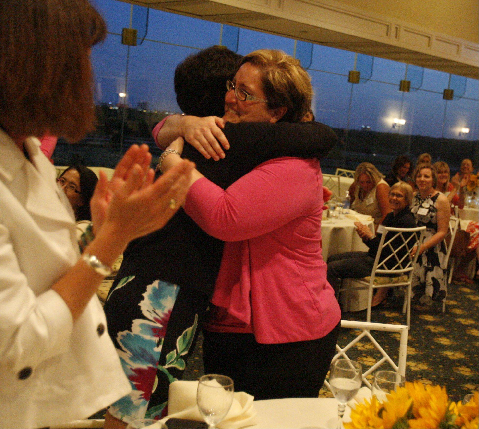 Noelle Moore, right, director of development for A Safe Place, gets a hug from Jean Spiegelhalter after an announcement that the organization was awarded $100,000 from Impact 100 Chicago, a philanthropic women´s organization, at a gala at Arlington Park in Arlington Heights on Tuesday. 142 women each made a tax-deductible donation of $1,000. The funds are pooled to create a $100,000 grant and three $14,000 finalist grants.