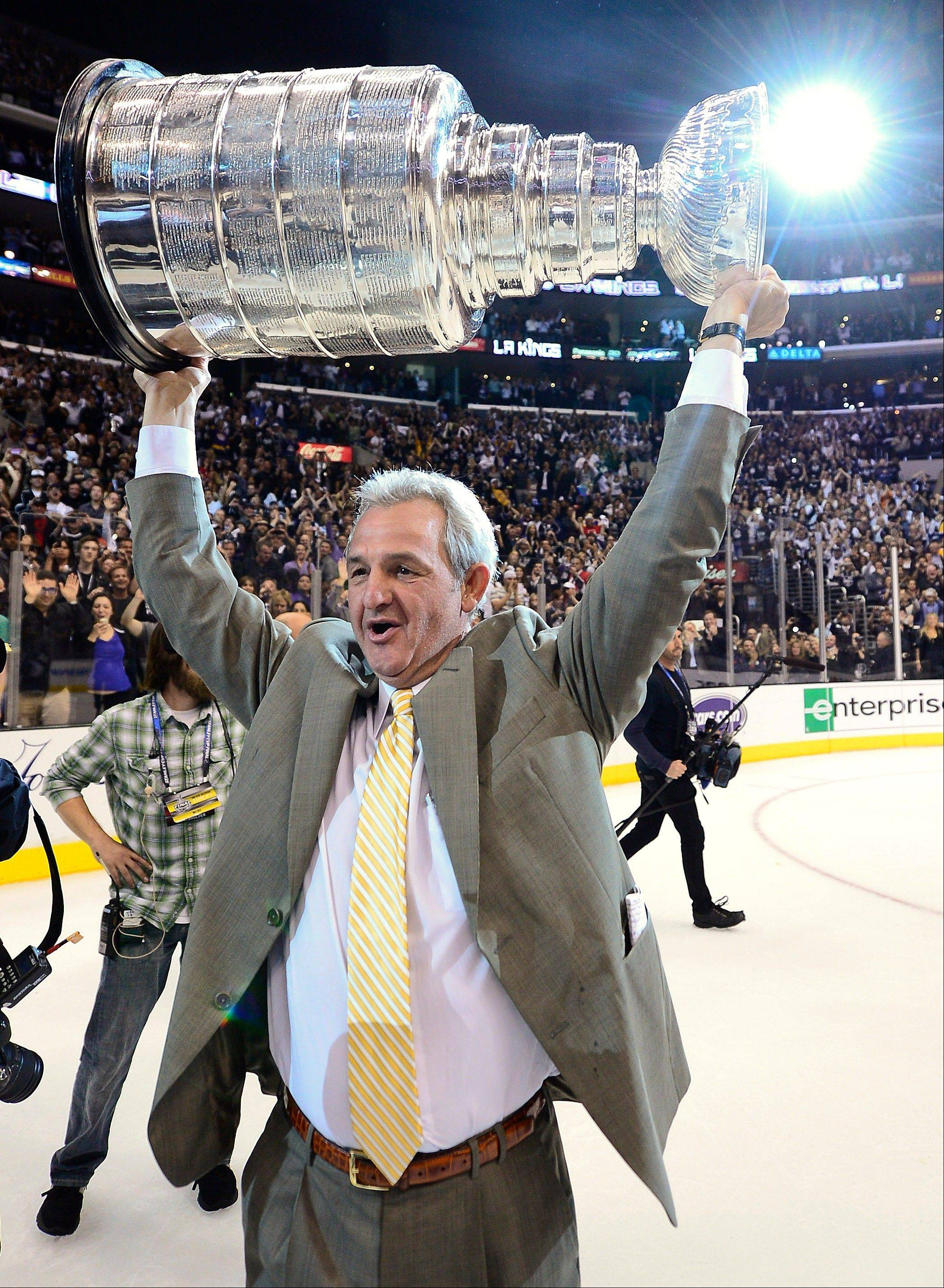 Los Angeles Kings coach Darryl Sutter hoists the Stanley Cup after beating the New Jersey Devils 6-1 during Game 6 of the Stanley Cup Finals.