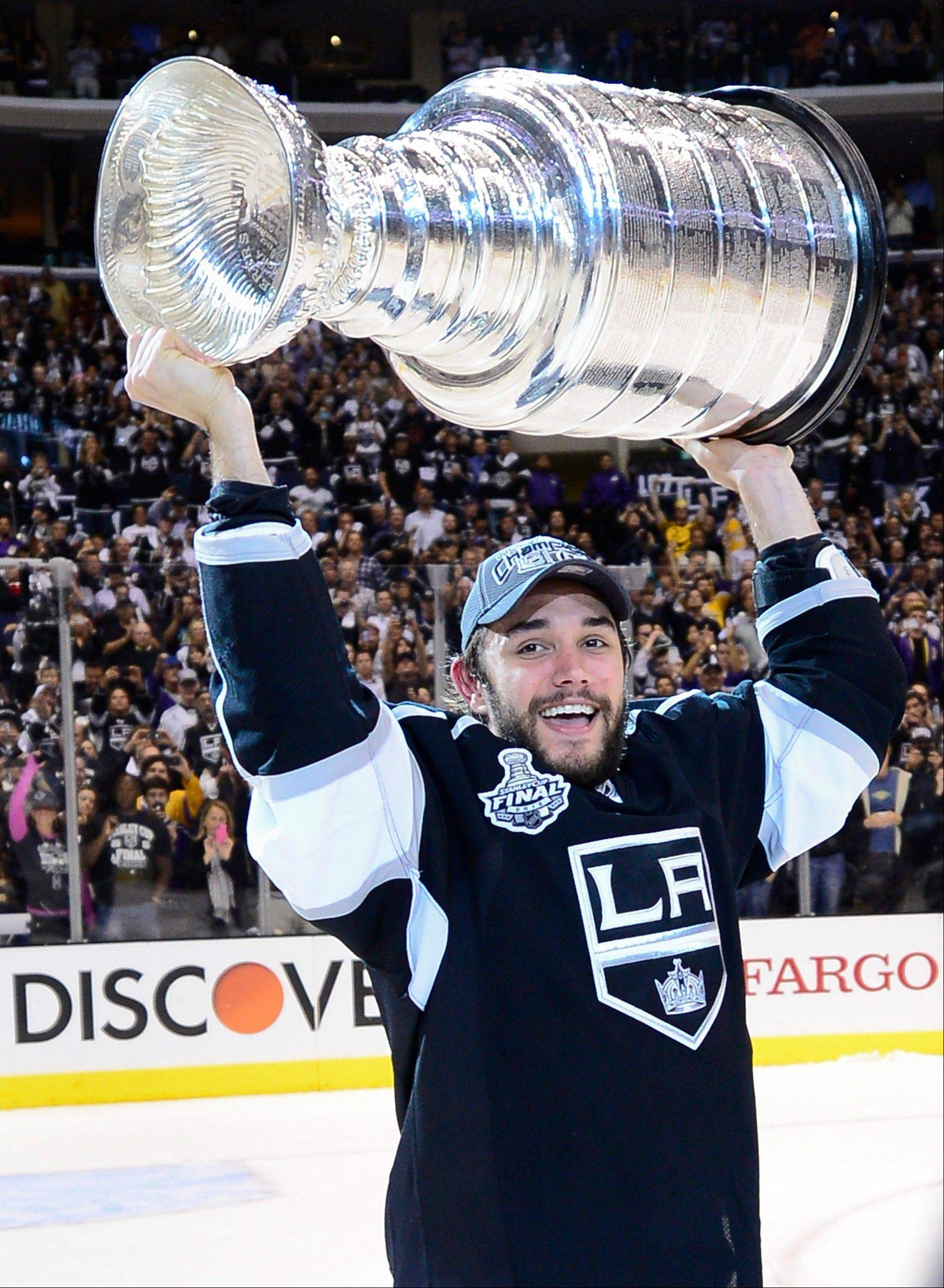 Los Angeles Kings defenseman Slava Voynov holds up the Stanley Cup Monday after the Kings beat the New Jersey Devils 6-1.