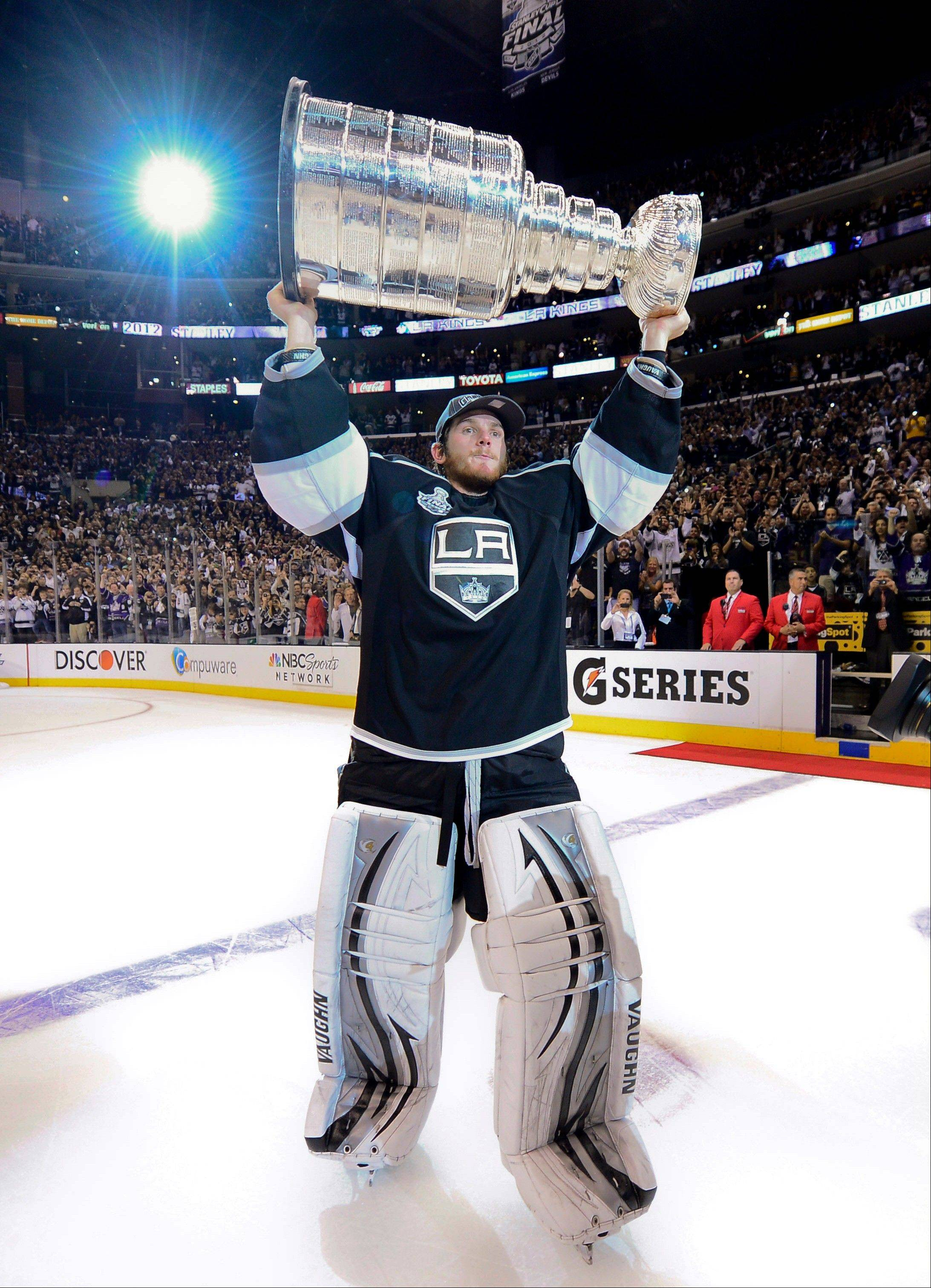 Los Angeles Kings goalie Jonathan Quick holds up the Stanley Cup after the Kings beat the New Jersey Devils.