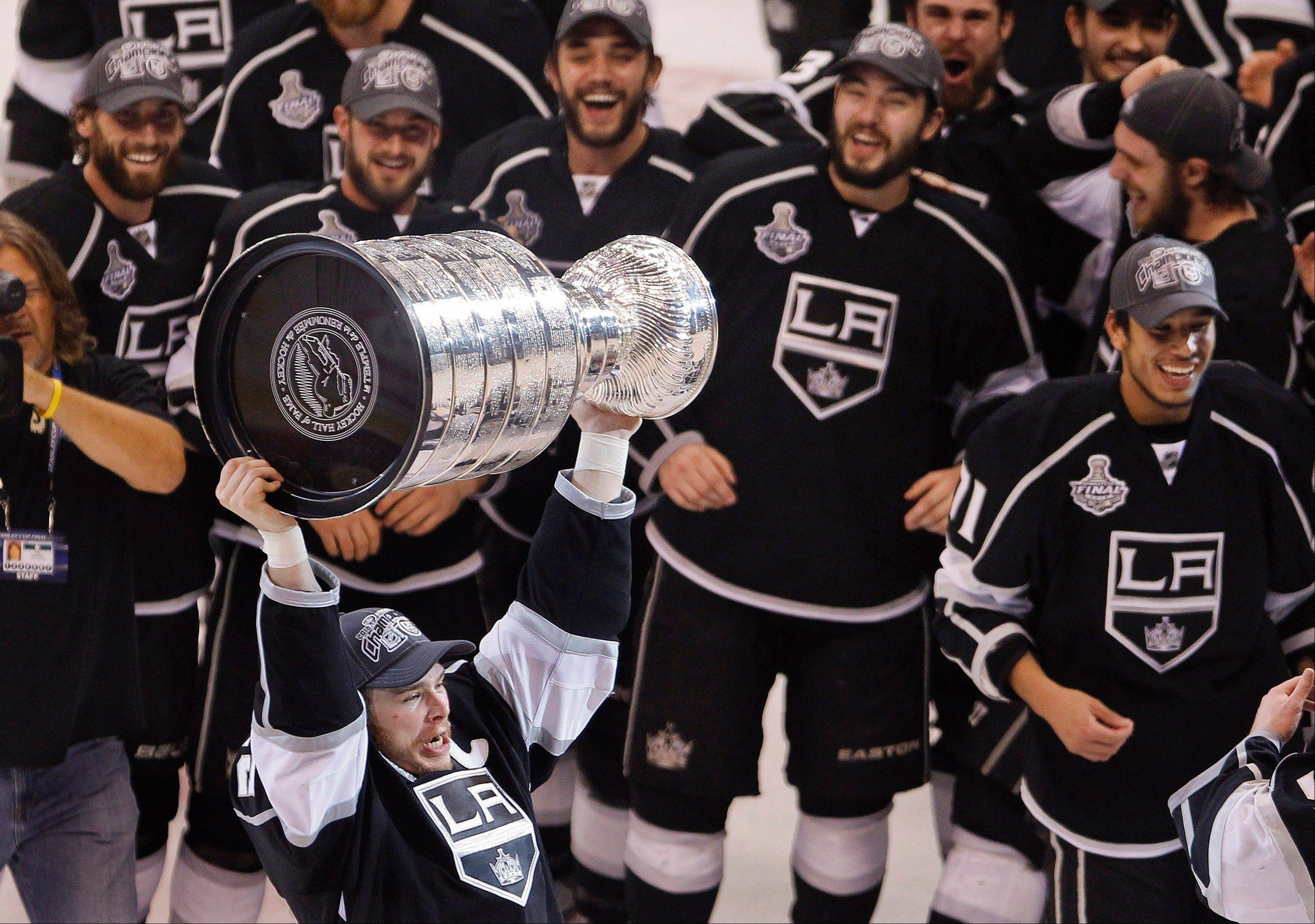 Los Angeles Kings captain Dustin Brown holds up the Stanley Cup.