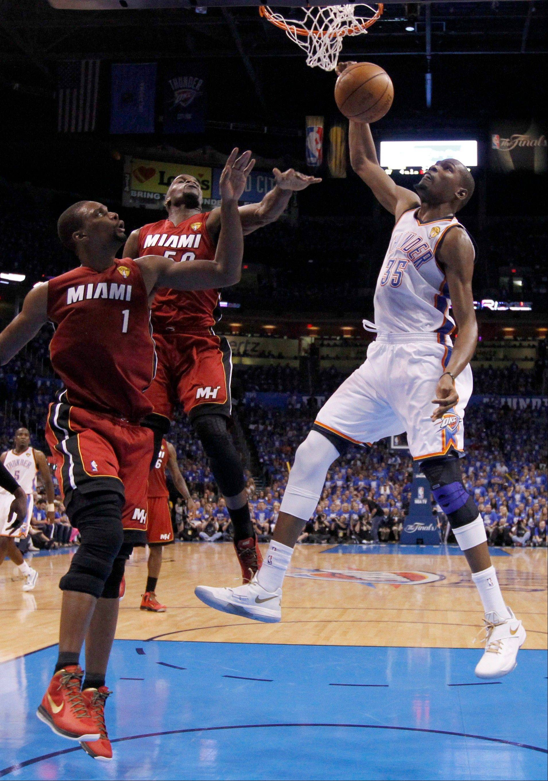 Oklahoma City Thunder small forward Kevin Durant (35) dunks as Miami Heat power forward Chris Bosh and center Joel Anthony defend during the first half Tuesday during Game 1 of the NBA Finals in Oklahoma City.