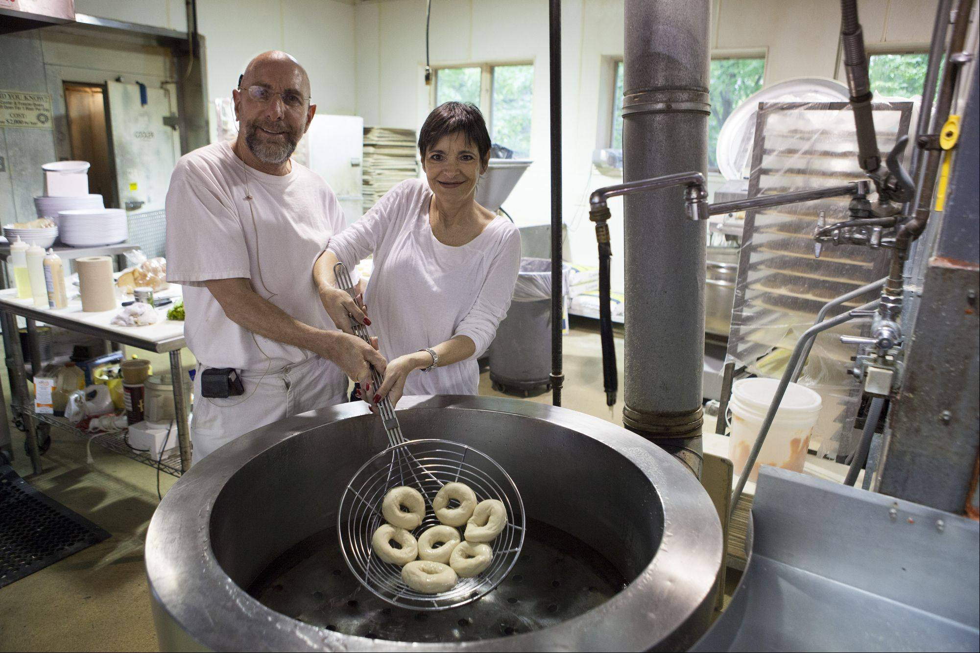 Harold and Sharon Harkavy hold bagels over where they are boiled before being baked. They are the owners of Chicago Bagel and Bialy, which turns 30 years old in July.