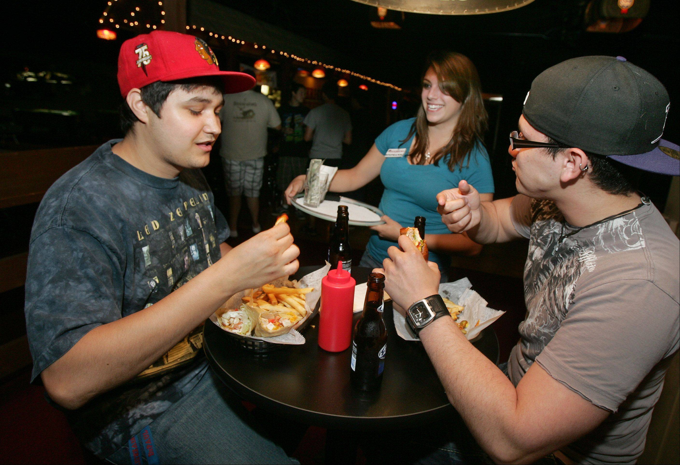 Brandon Ivanovic, left, and Danny Servellon, both of Libertyville, talk to waitress Stephanie Van Kooten as they enjoy dinner at Mavericks Night Club in Mundelein.