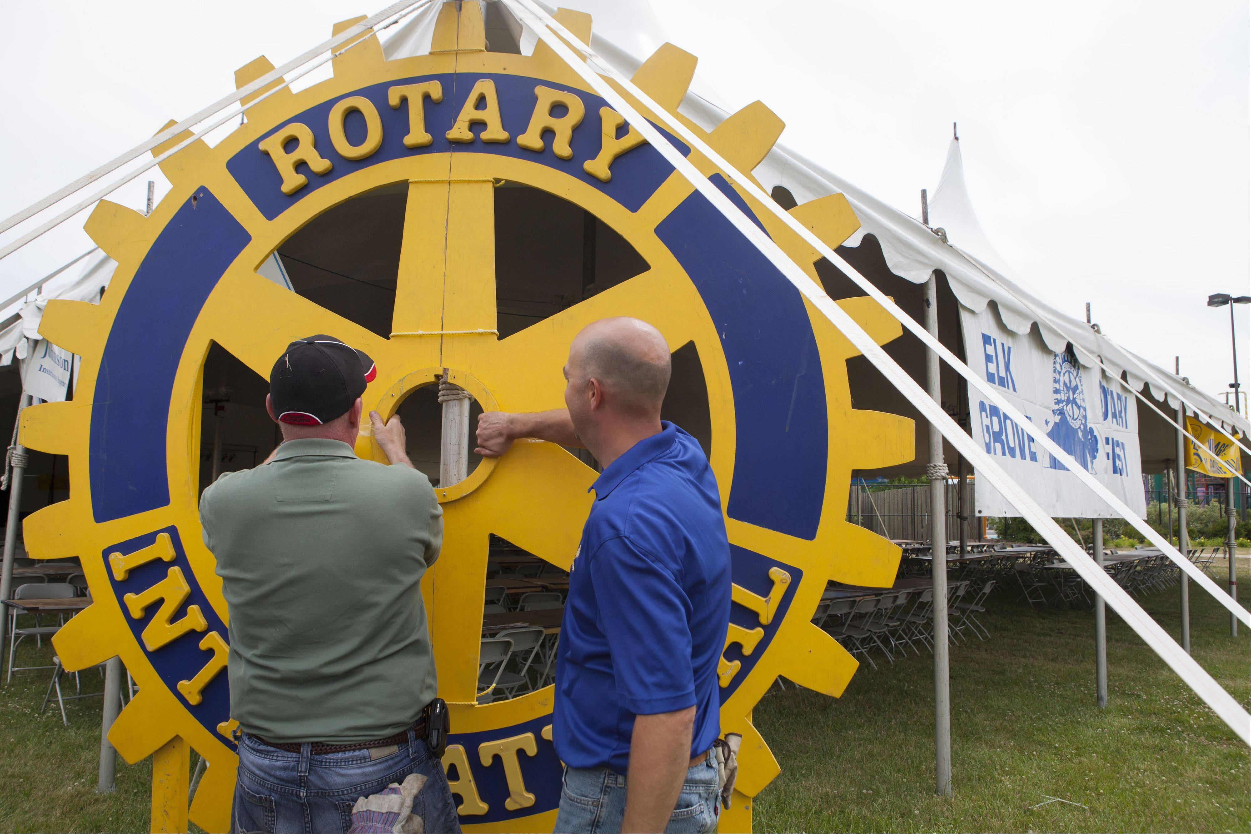 "Bill Beaupre, left, and Bill Martson, who have been part of Elk Grove Village Rotary Club for almost 20 years, put the finishing touches on the ""Rotary International"" wheel for RotaryFest, which continues through Sunday. The event includes carnival rides and live musical entertainment."