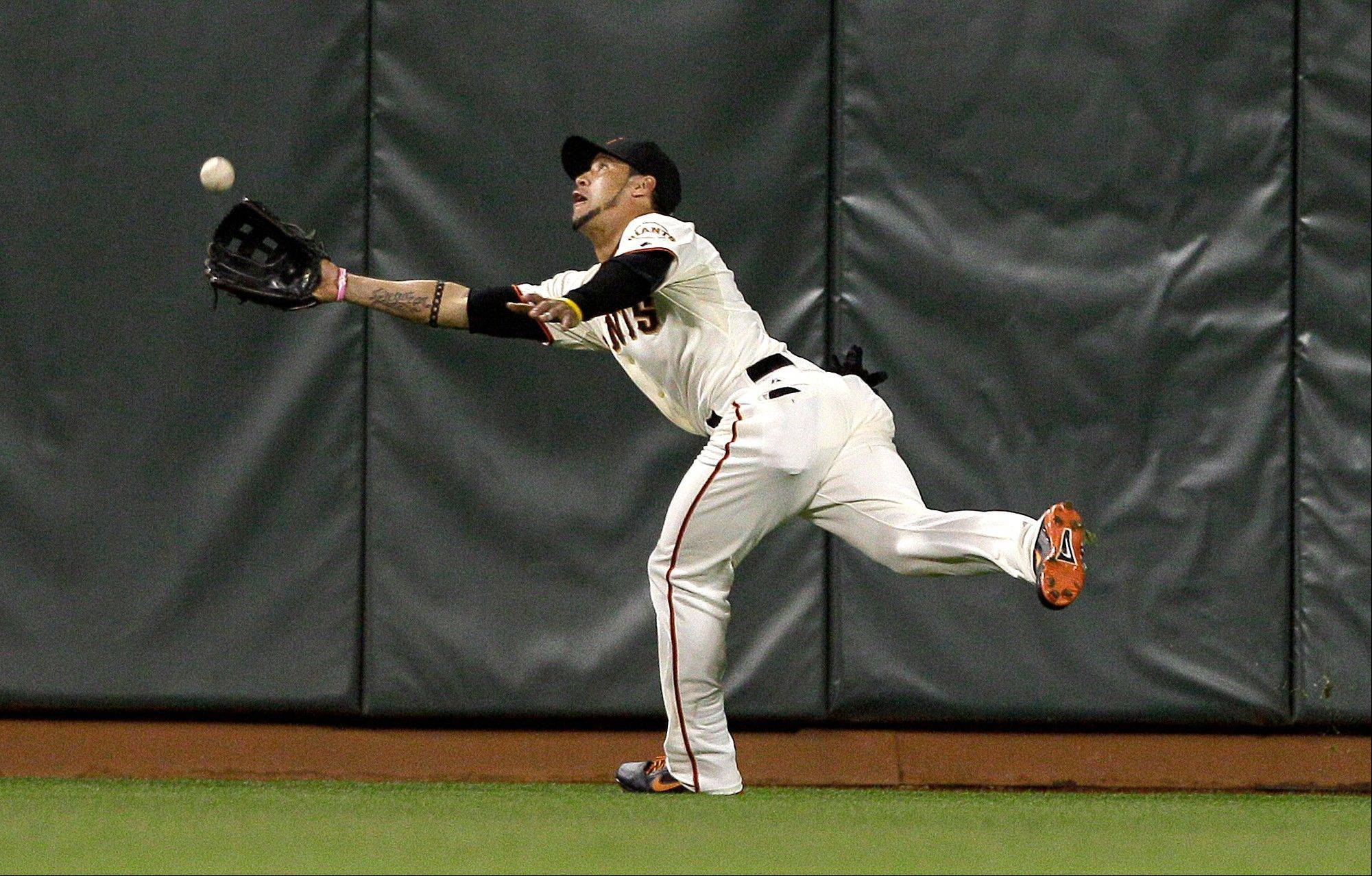 Giants center fielder Gregor Blanco catches a fly ball hit by Houston Astros' Jordan Schafer during the seventh inning Wednesday to help preserve pitcher Matt Cain's perfect game.