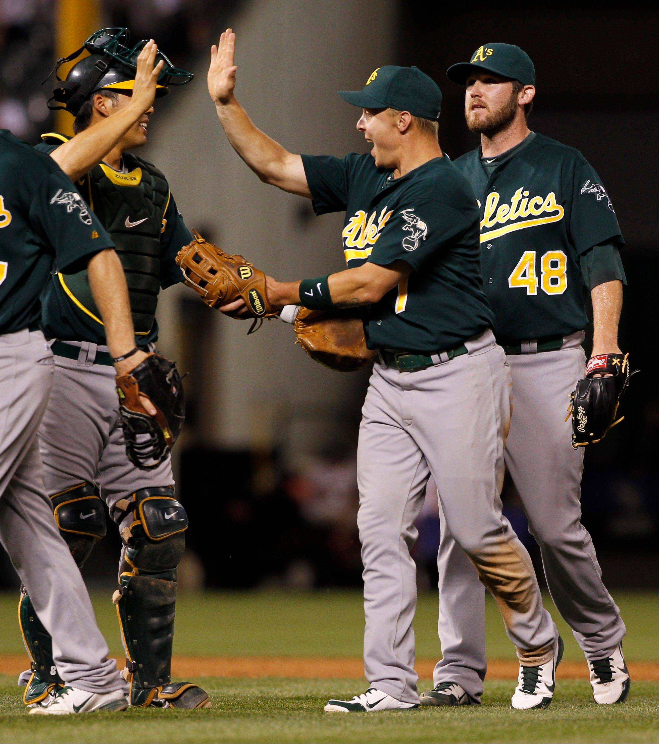 Oakland catcher Kurt Suzuki, left, celebrates with third baseman Brandon Inge, center, and relief pitcher Ryan Cook after the Athletics' 10-8 victory over the Rockies Wednesday in Denver.
