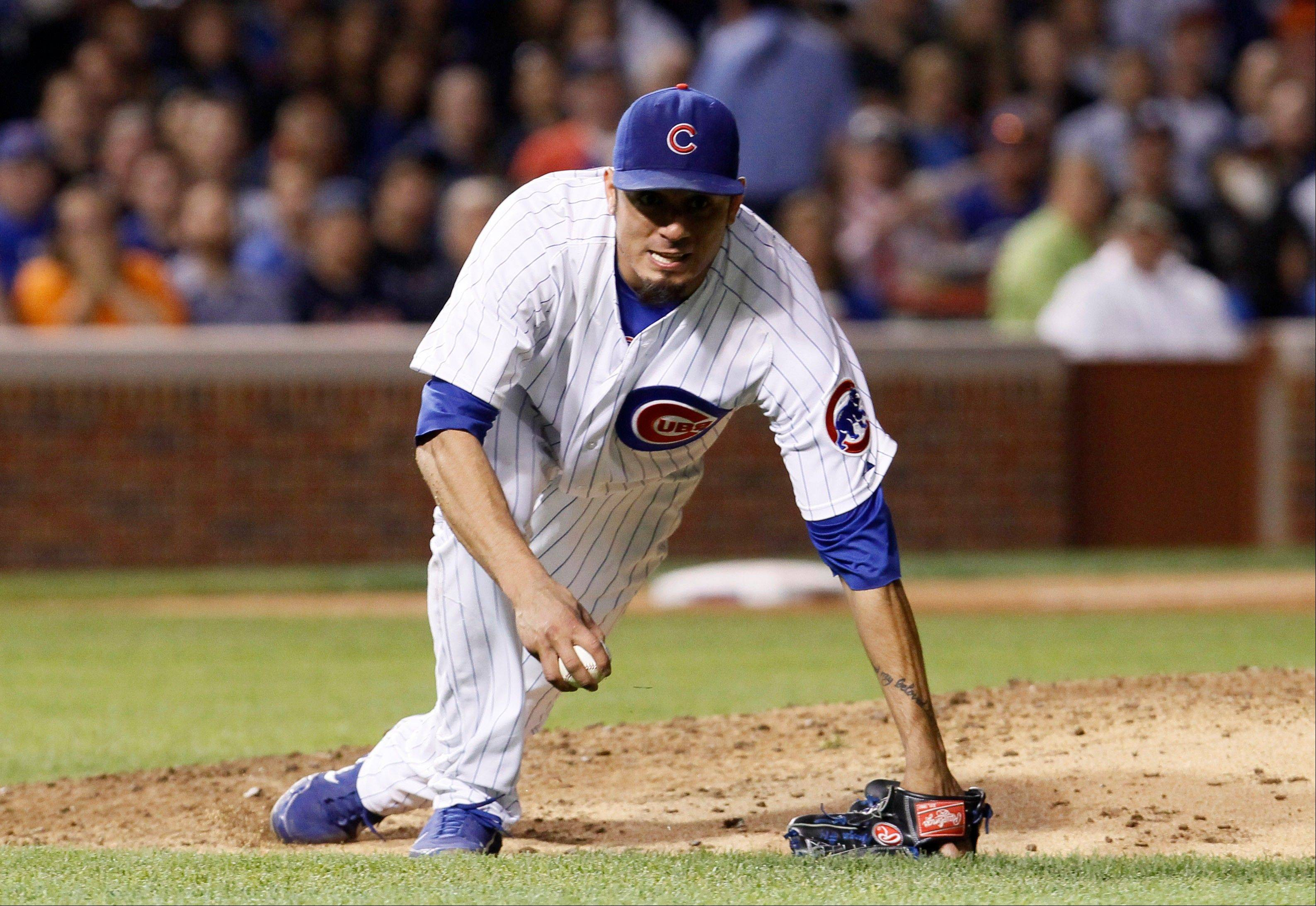 Cubs starting pitcher Matt Garza recovers after being knocked to the ground fielding a ball hit by the Detroit Tigers' Ramon Santiago Wednesday during the sixth inning at Wrigley Field. Jhonny Peralta scored on the play.