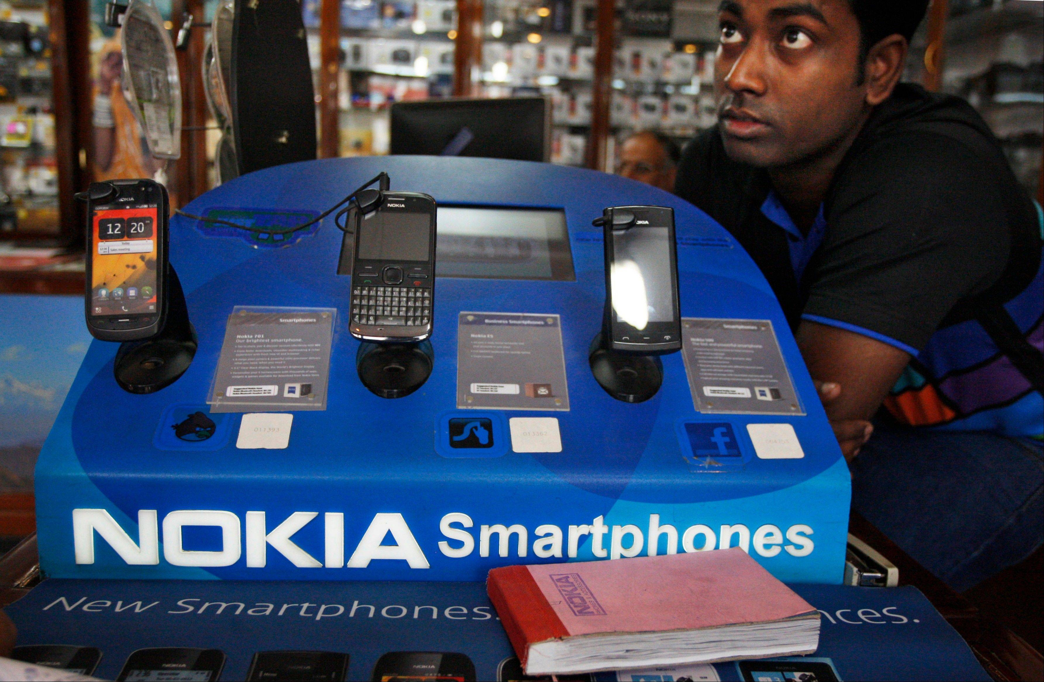 An Indian shopkeeper selling Nokia mobile phones awaits customers in New Delhi, India, Thursday. Nokia Corp. will lay off 10,000 jobs globally and close plants by the end of 2013, the company said Thursday.
