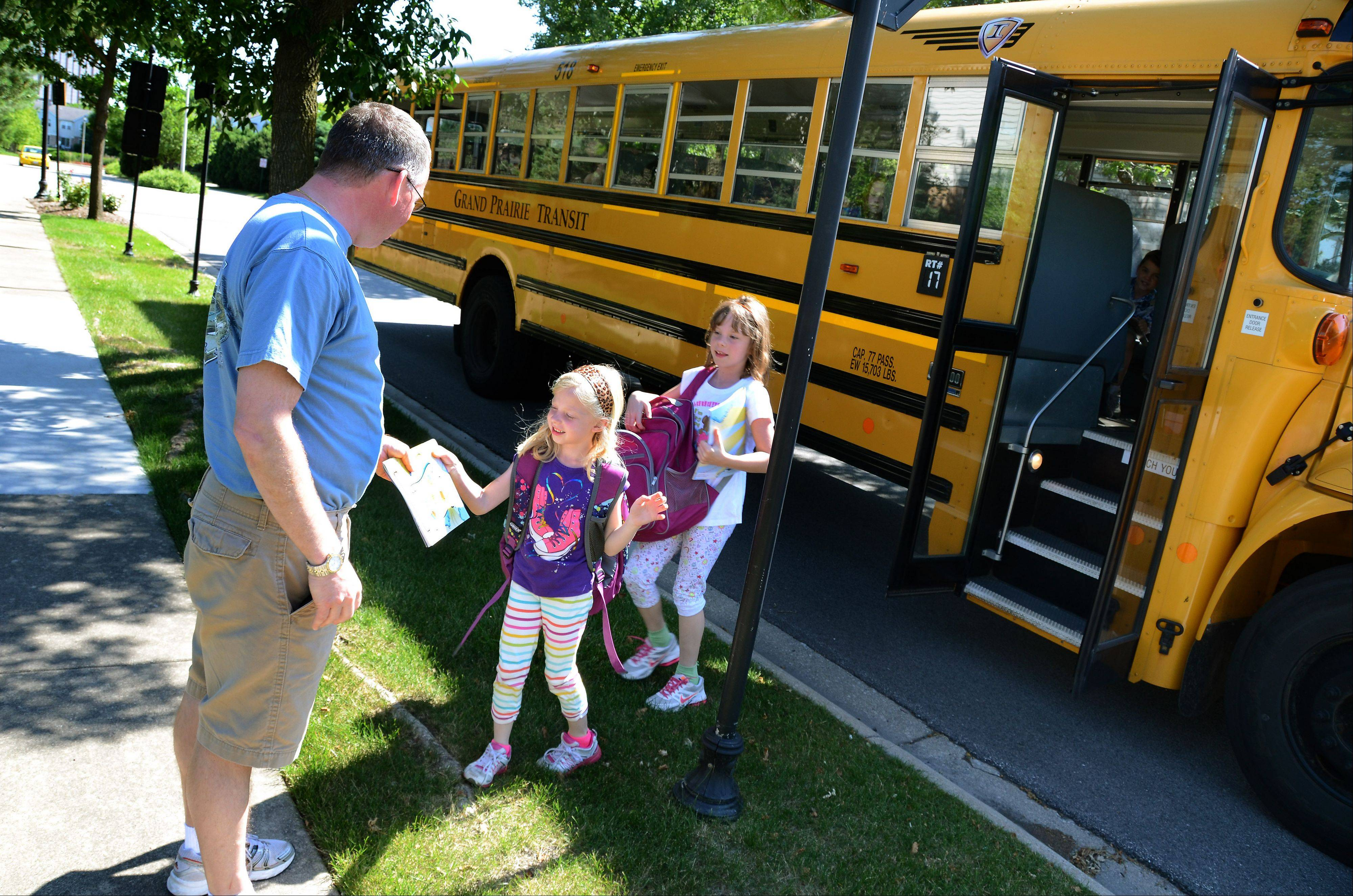 Stay-at-home dad Randy Reid meets his daughters Maddie, 6, left, and Bella, 8, home from the bus stop.