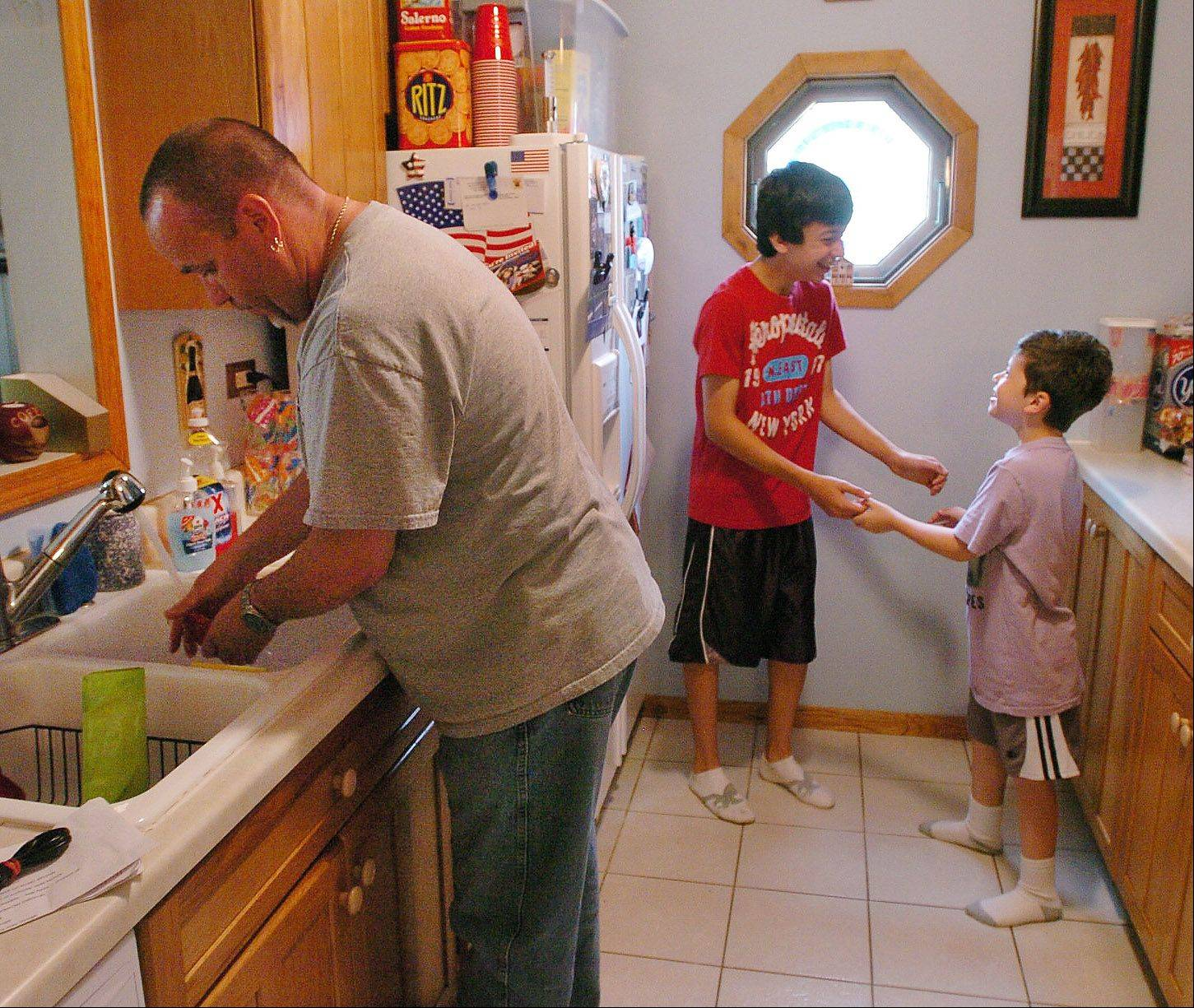 Stay at home dad Scott Kennelly in the kitchen with his two sons Logan and Michael.